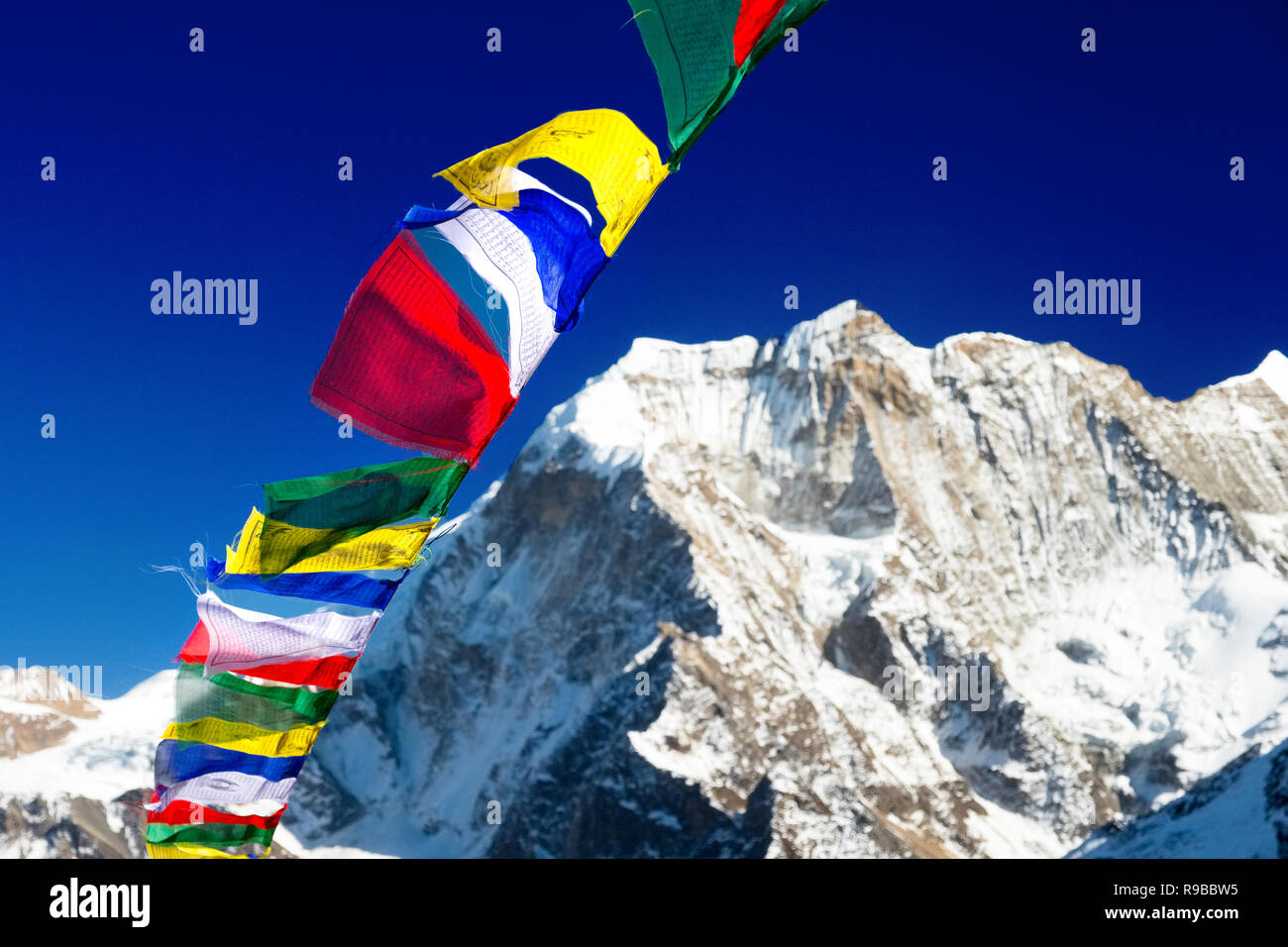 Prayer flags, blue sky and Himalayan mountain in the Manaslu region, Nepal - Stock Image