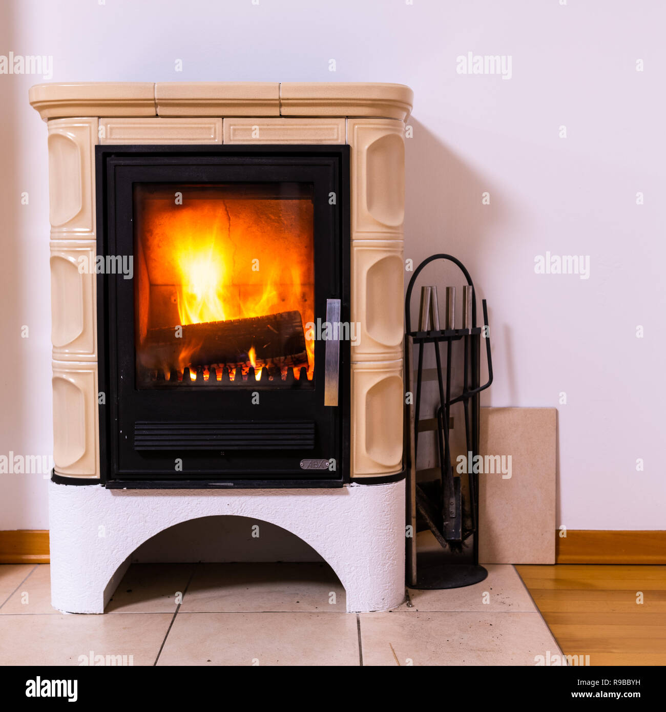 Tiled stove with fire burning inside, cosy and warm interior scene, heating in winter - Stock Image