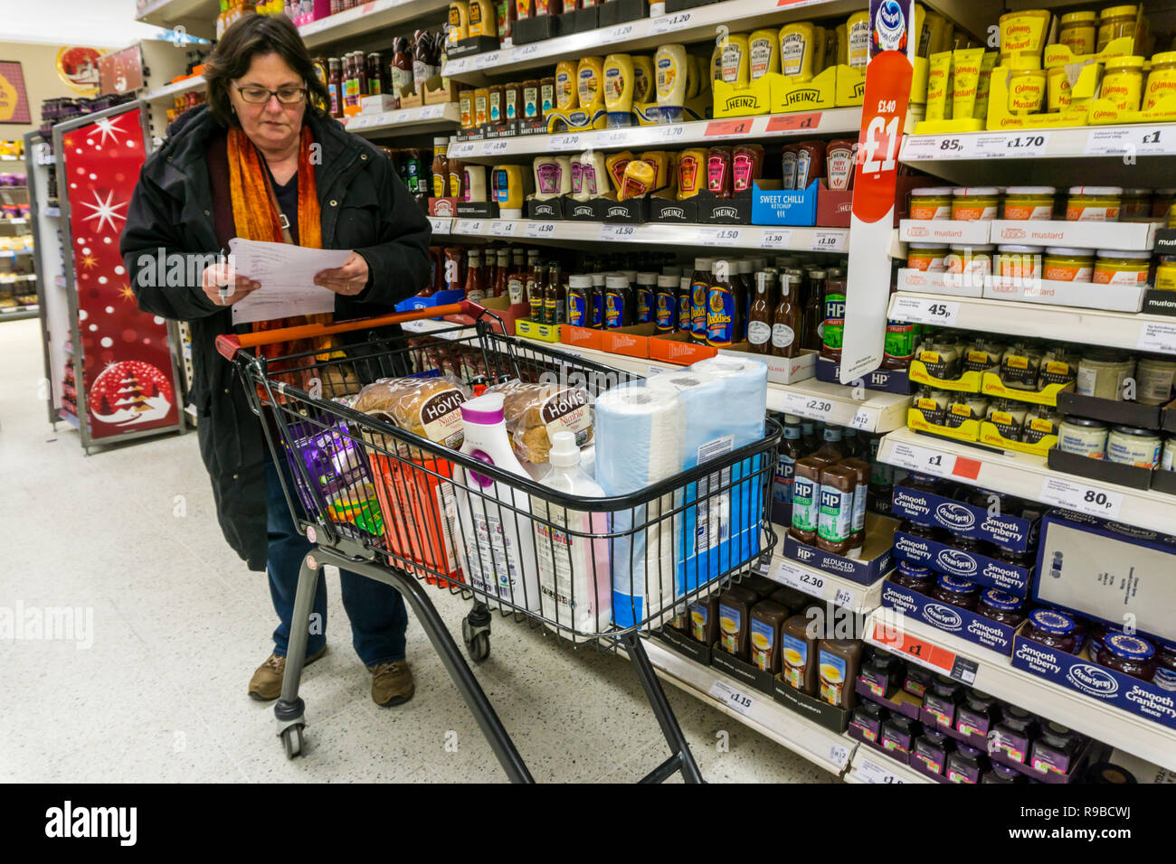 Woman checking a handwritten shopping list next to a full supermarket trolley.  Harassed, worried last minute shopping. - Stock Image