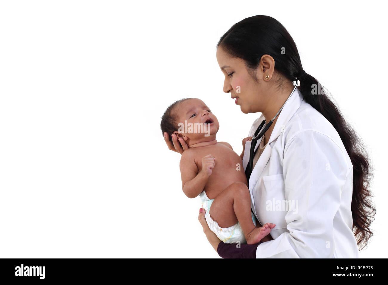 Cheerful female pediatrician holds newborn baby - Stock Image
