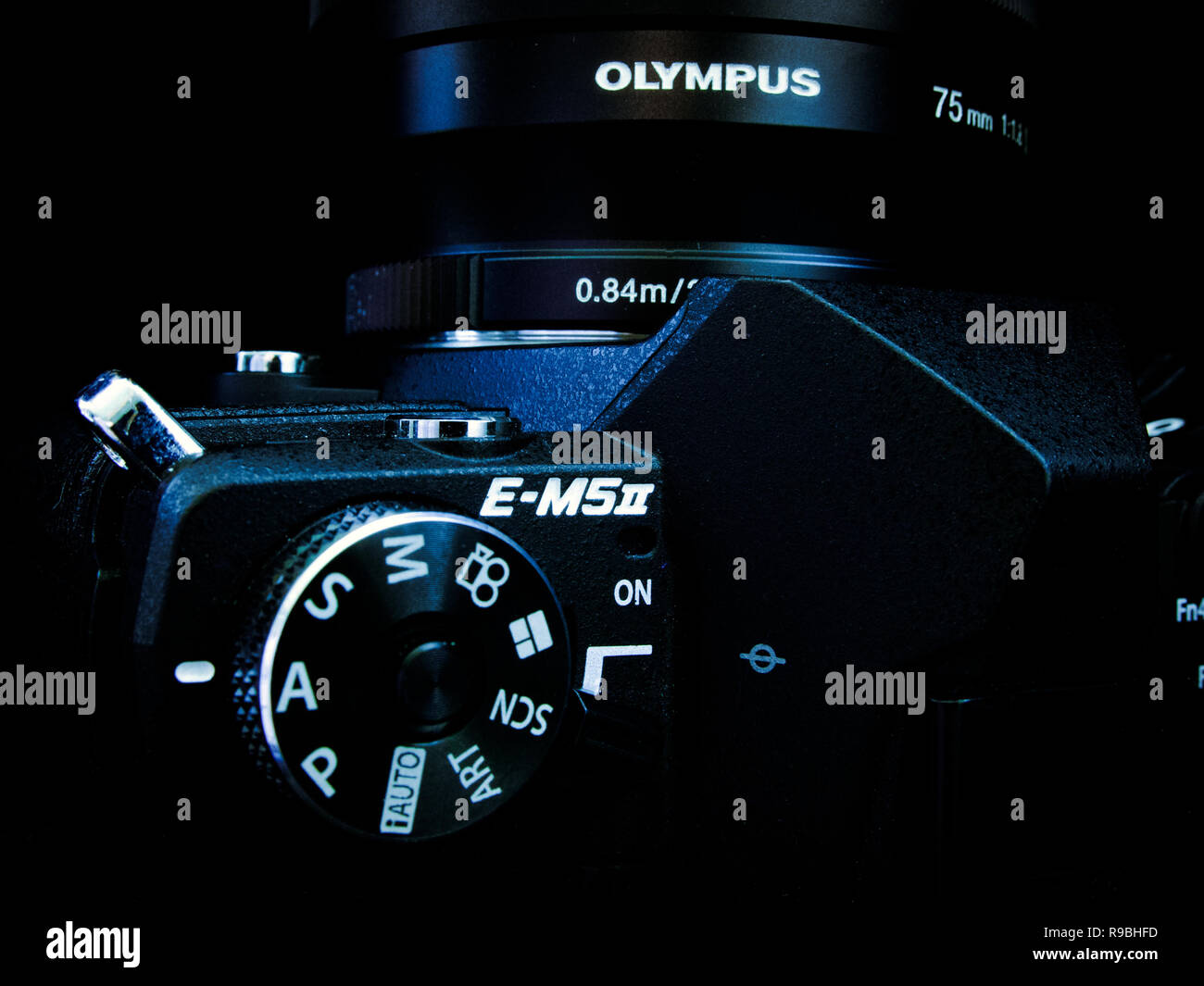 Belgium - Novemer 2018 : Close up Olympus MFT camer a with 75mm lens. Dark with blue shine. - Stock Image