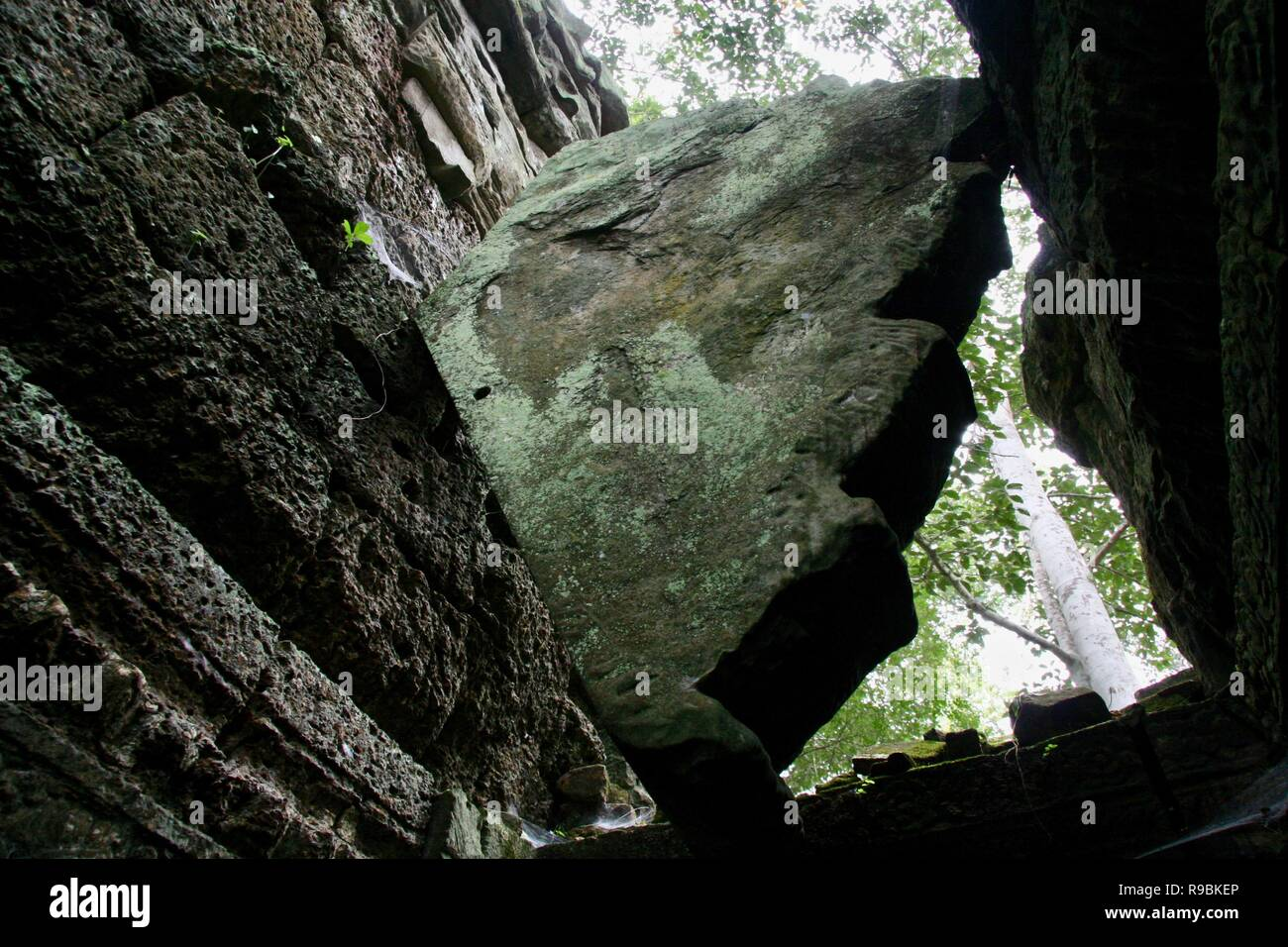 A huge rock caught and wedged between two stone walls - Stock Image