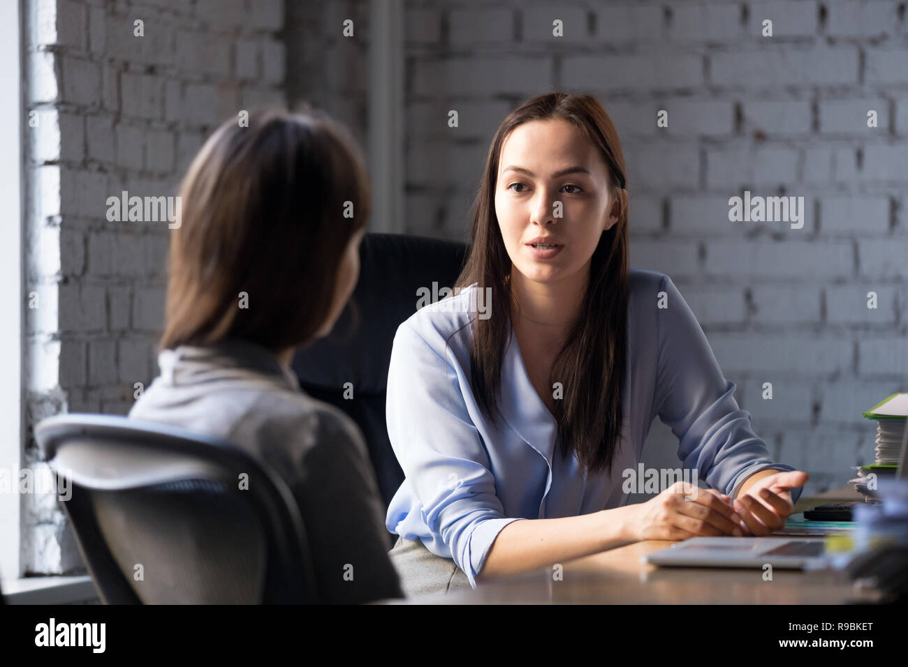 Serious professional female advisor consulting client at meeting - Stock Image