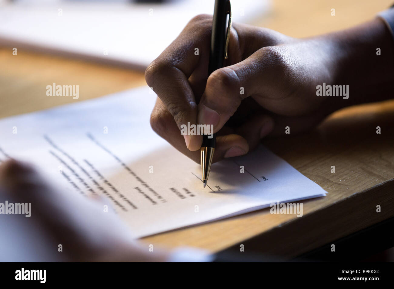 Male african hand write signature on legal corporate paper docum - Stock Image