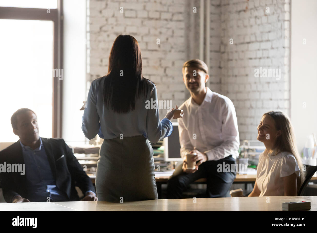 Rear view at female leader speaking at diverse group meeting Stock Photo