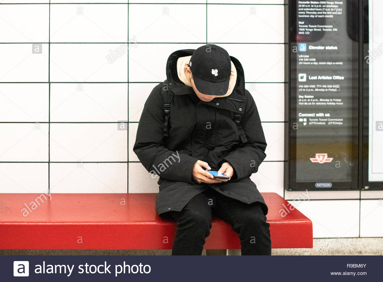 The technology attachment.  A young man browses his smartphone in a subway station. Most TTC stations have wifi already. City life and real people lif - Stock Image
