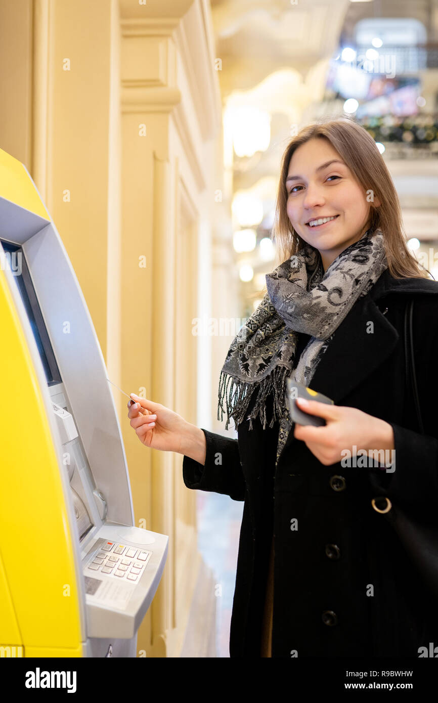 Photo of happy brunette with bank card at ATM on blurred background - Stock Image
