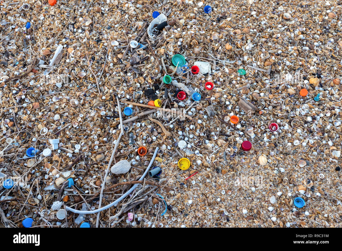 Plastic bottle caps scattered on the beach, environmental pollution - Stock Image