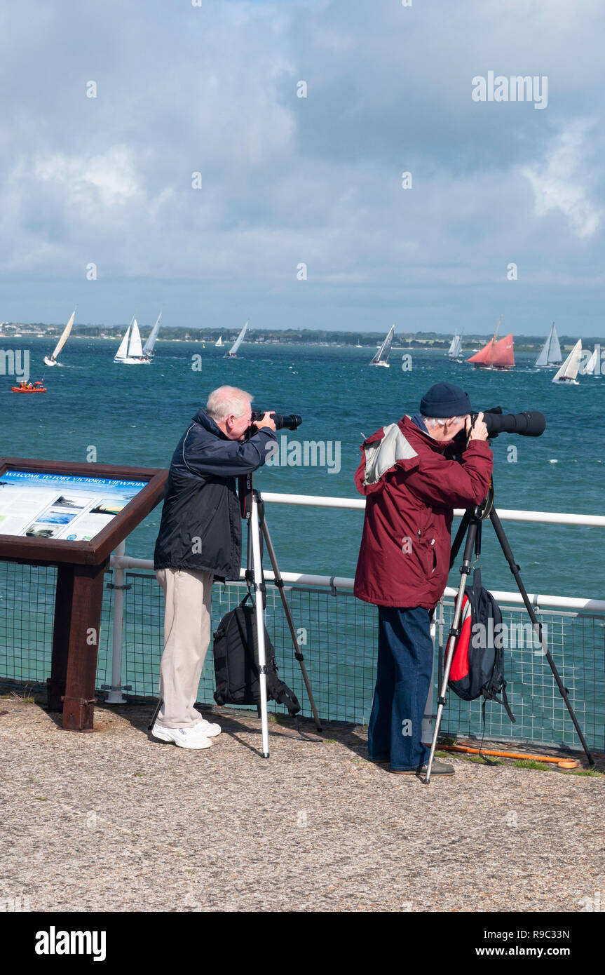 Two men photographing Round The Island Race from Fort Victoria, Isle of Wight - Stock Image