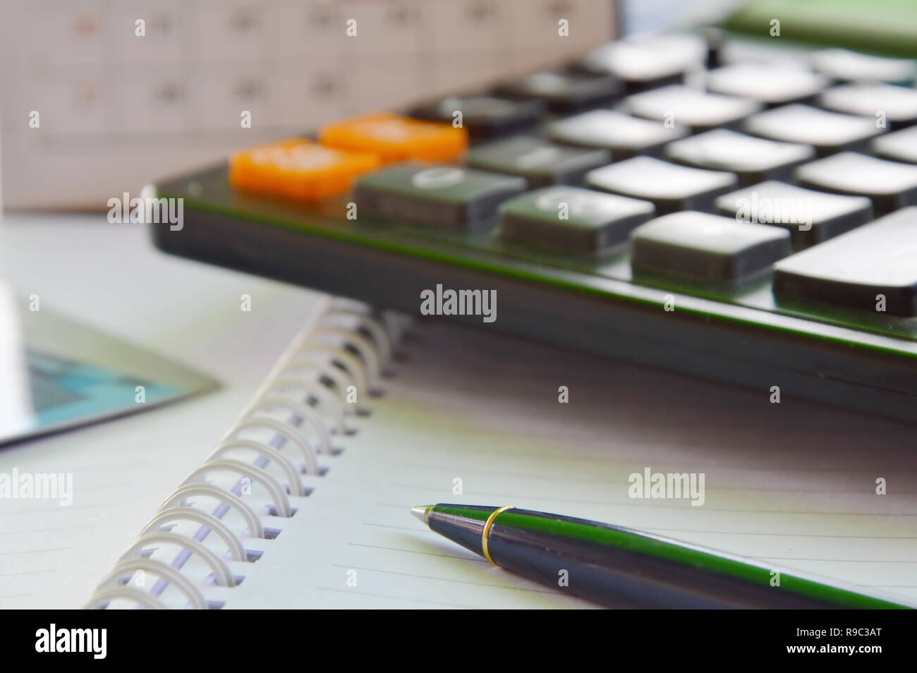 pen and calculator on the book - Stock Image