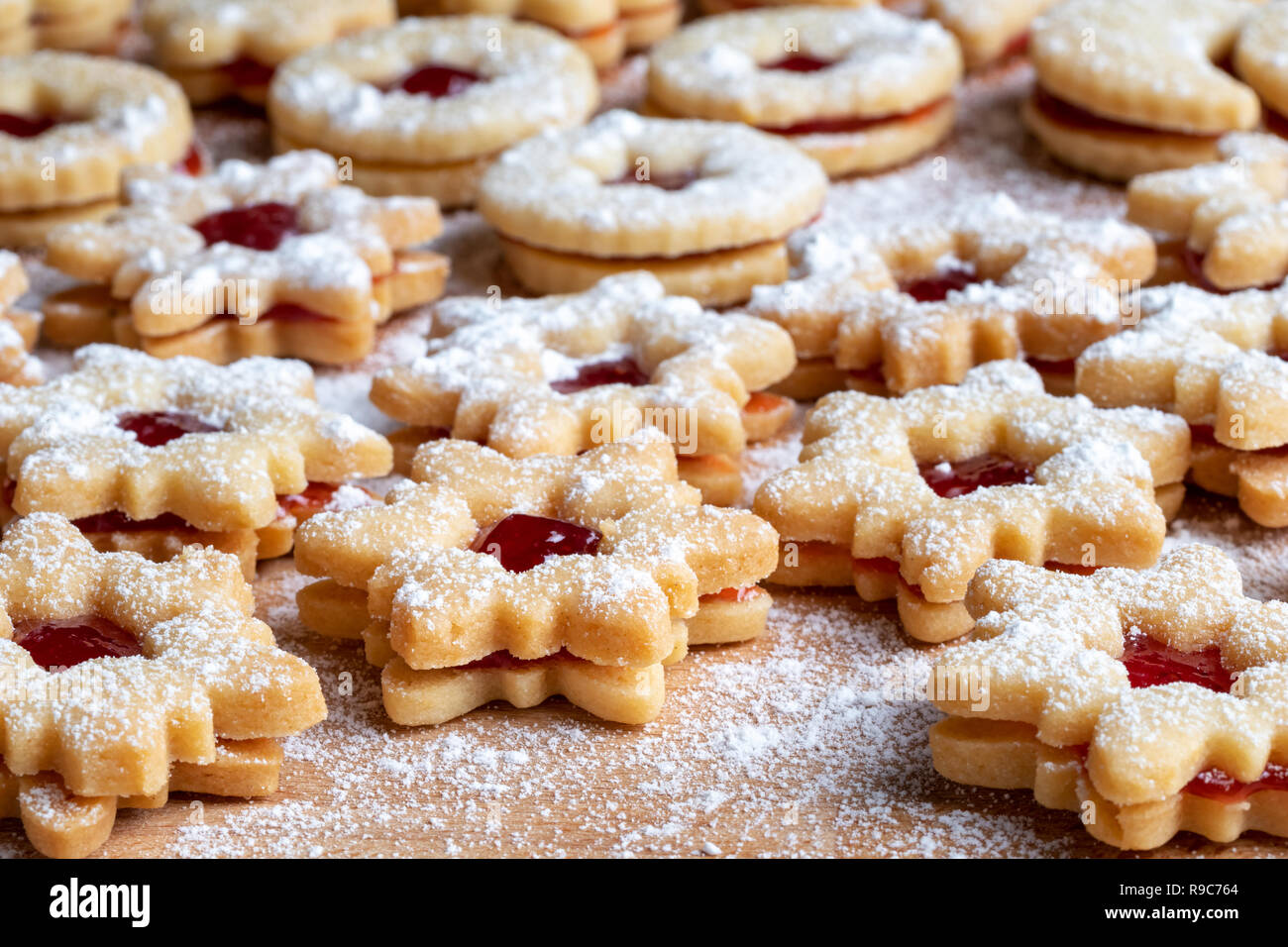 Traditional Linzer Christmas cookies filled with strawberry jam and dusted with sugar - Stock Image