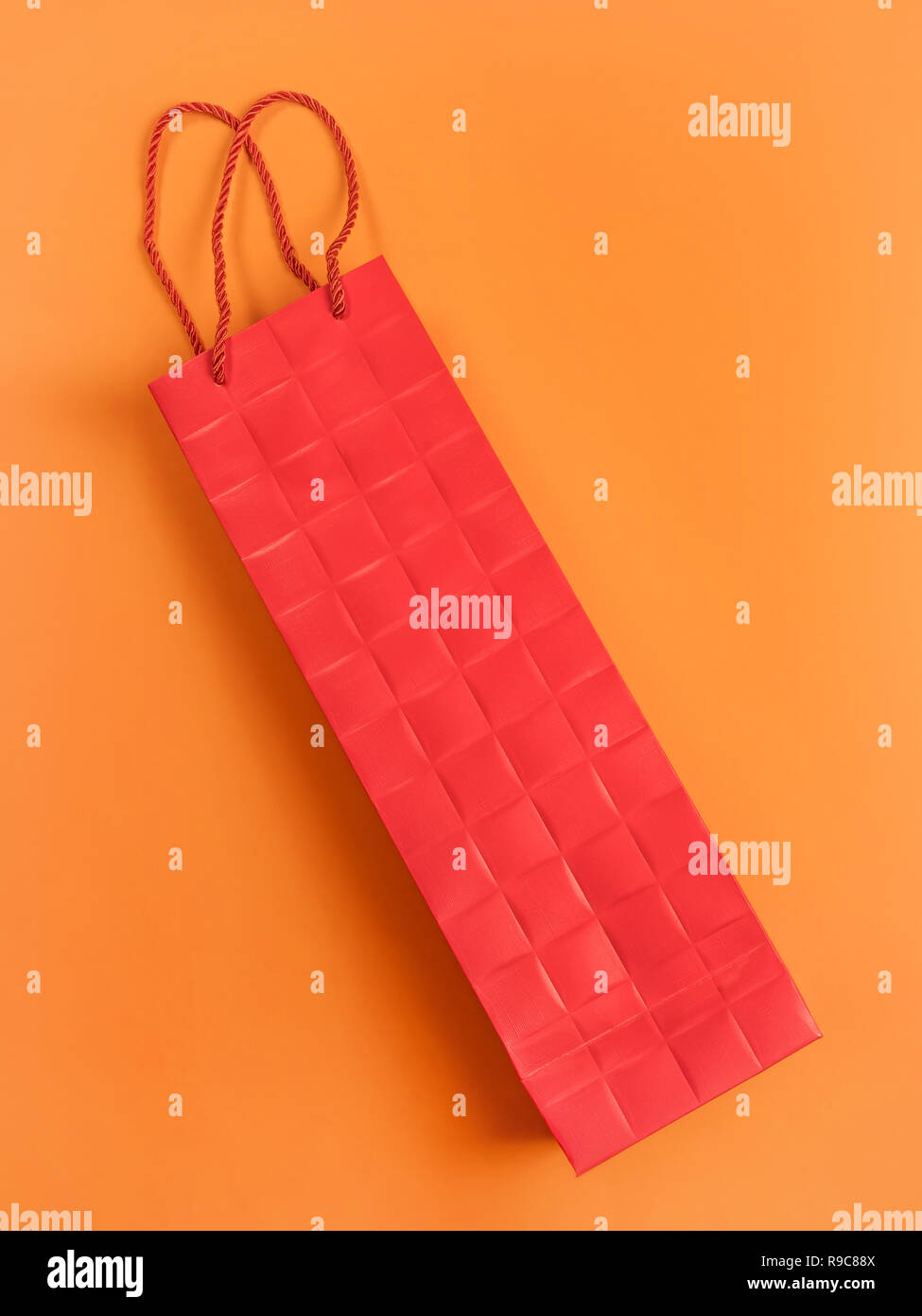 Red cardboard gift bag on orange. Sparse abstract composition. - Stock Image