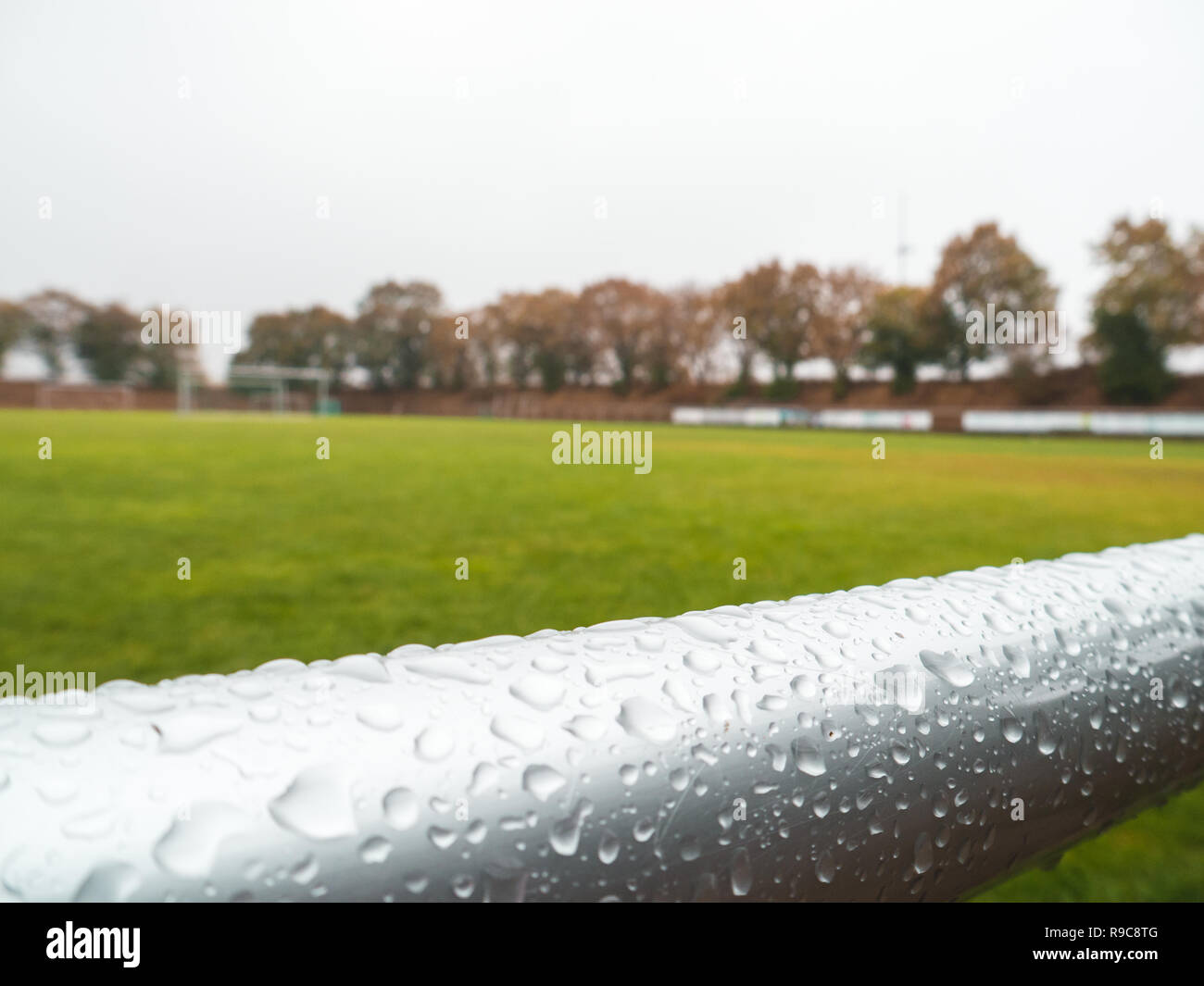 close-up shot of wet hand rails at Rural grass soccer pitch in Germany - Stock Image