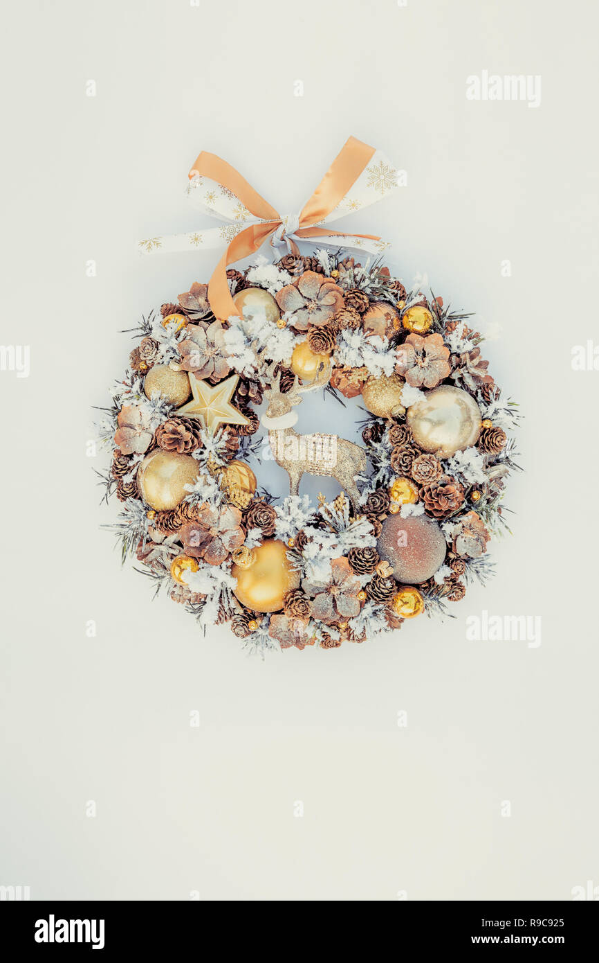 Top view golden Christmas wreath decorated with pine cones, ornamentals, spruce branches, balls, stars and decorative deer on black wooden background, - Stock Image