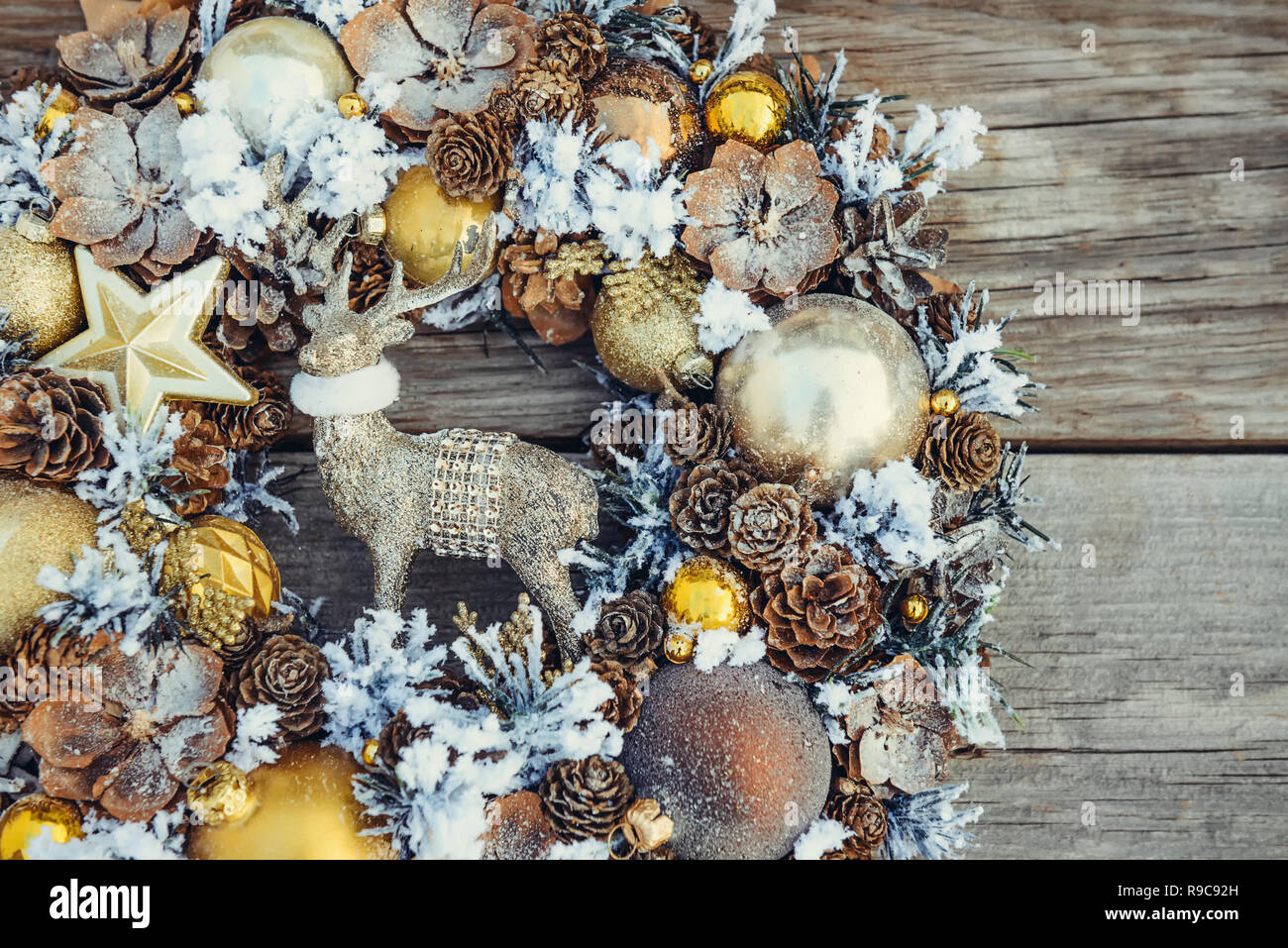 Top view Beautiful hand made golden Christmas wreath decorated with pine cones, ornamentals, spruce branches, balls, stars, decorative deer on rustic  - Stock Image