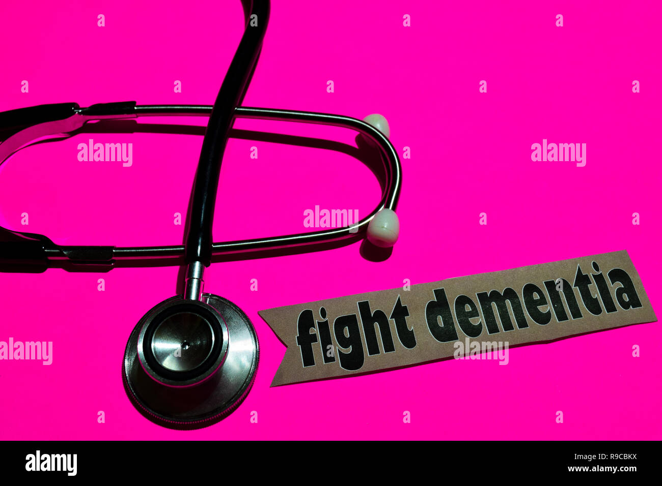 Fight dementia on the paper with healthcare concept Inspiration. stethoscope on pink bakcground - Stock Image