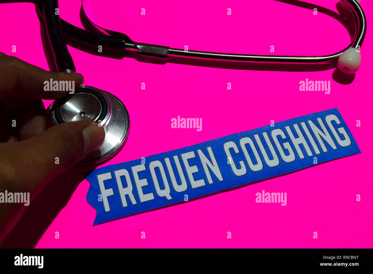 Frequen coughing on the paper with healthcare concept. With stethoscope on pink bakcground - Stock Image