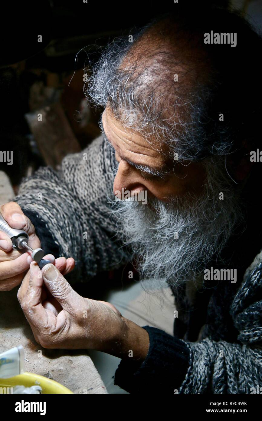 An old jeweller polishing a jade pendant under a light in his workshop - Stock Image