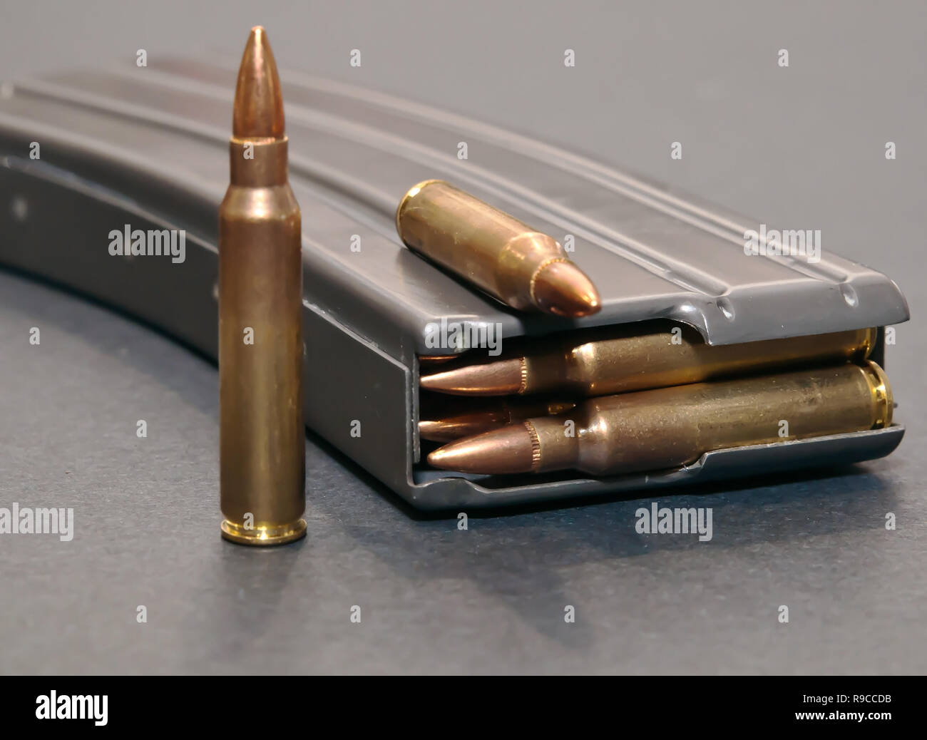 A rifle magazine loaded with .223 bullets on a gray background with two extra bullets - Stock Image