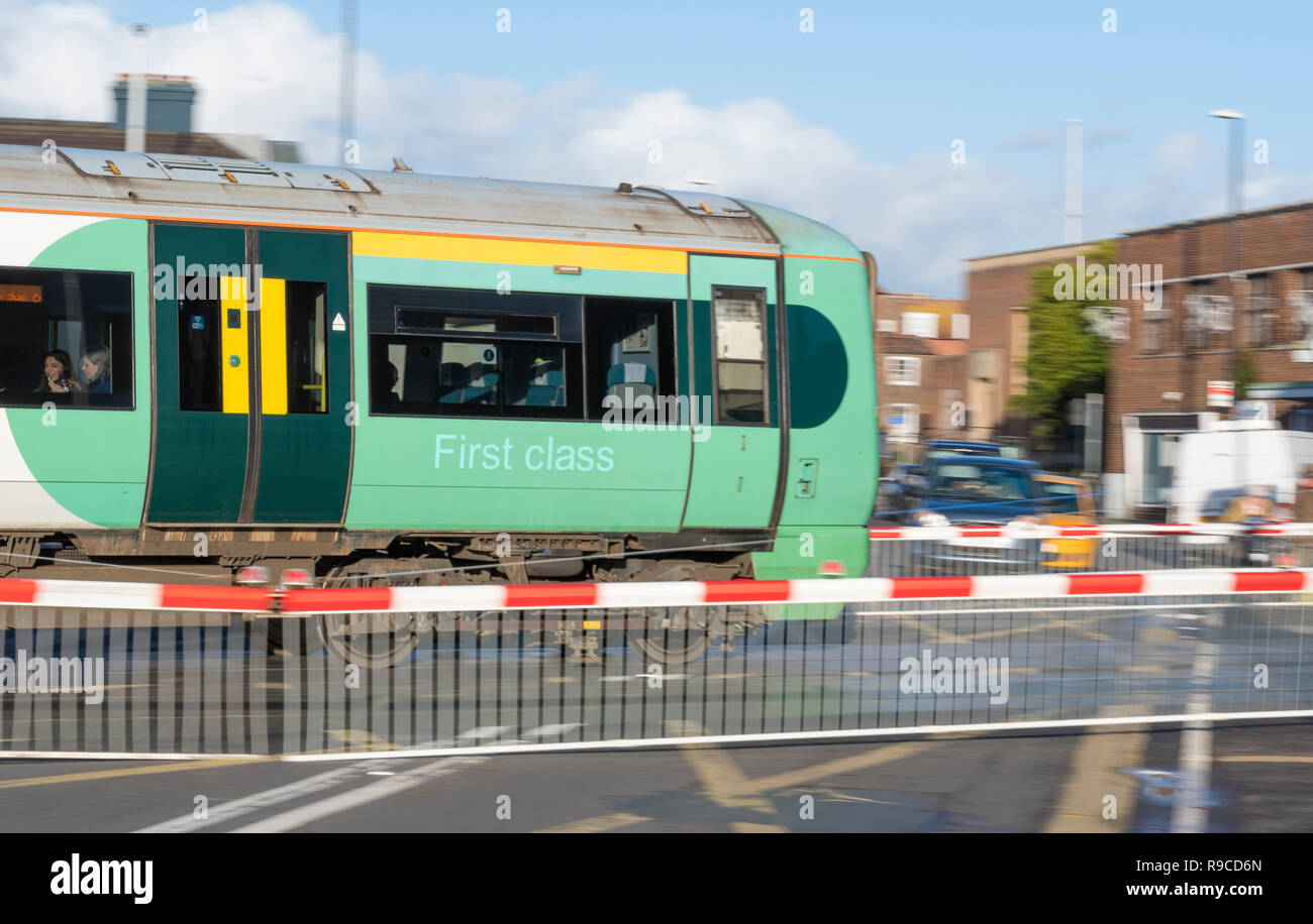 Southern Rail Class 377 Electrostar locomotive and first class carriage on a train on a level crossing in West Sussex, England, UK. Class 377 loco. - Stock Image