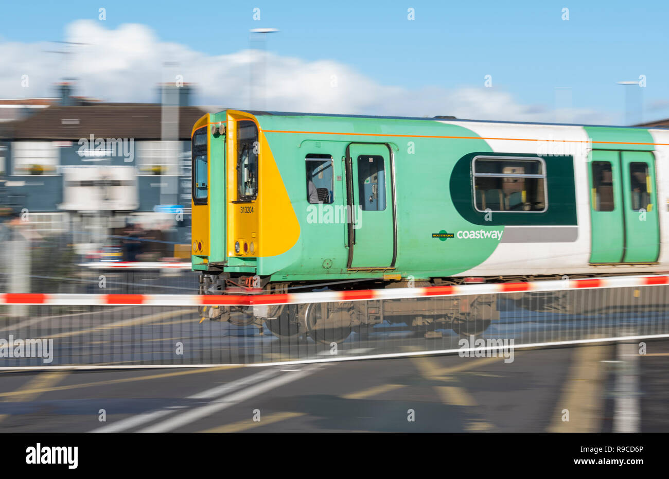 Southern Rail Coastway Class 313 locomotive and train on a level crossing in West Sussex, England, UK. Class 313 loco. - Stock Image