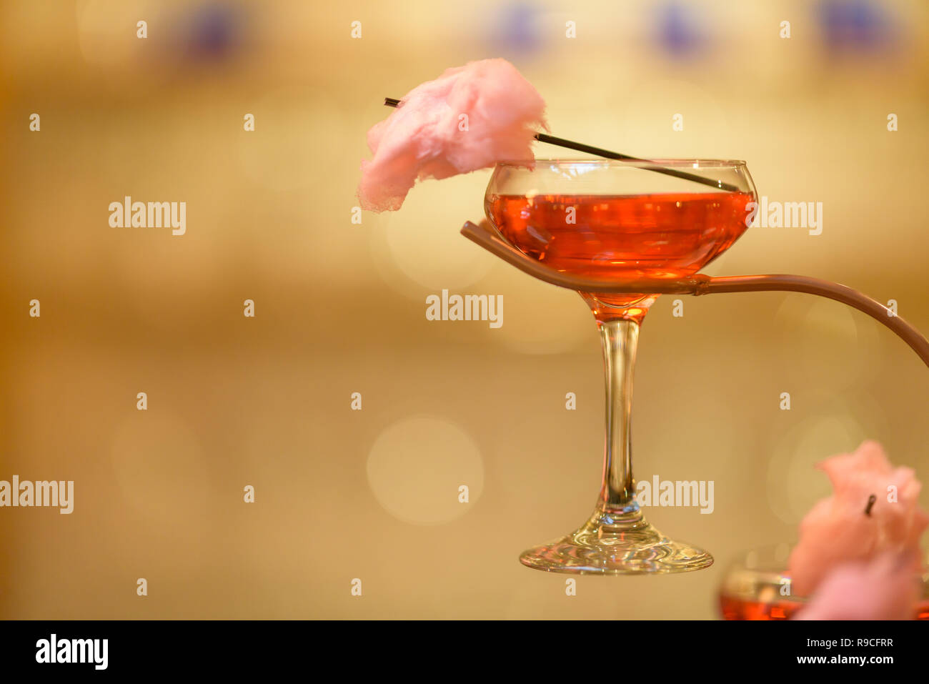 Candy floss cocktail on cocktail tree with straw holding piece of candy floss. Pink cotton candy. Landscape format image in high resolution, - Stock Image