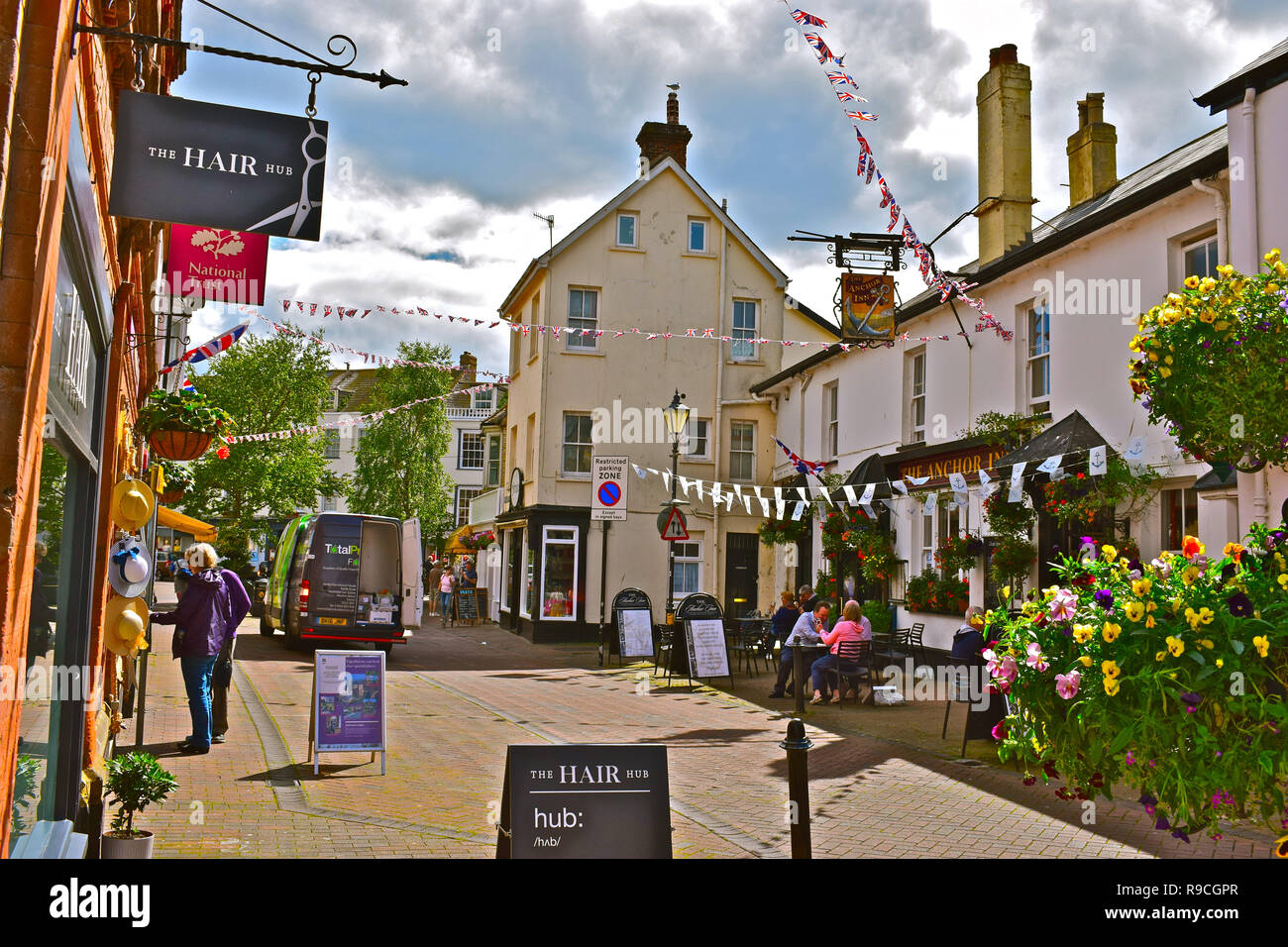 The town centre of Sidmouth with colourful bunting, hanging baskets,  and leafy trees. People enjoying a relaxing drink outside the Anchor Inn pub. - Stock Image
