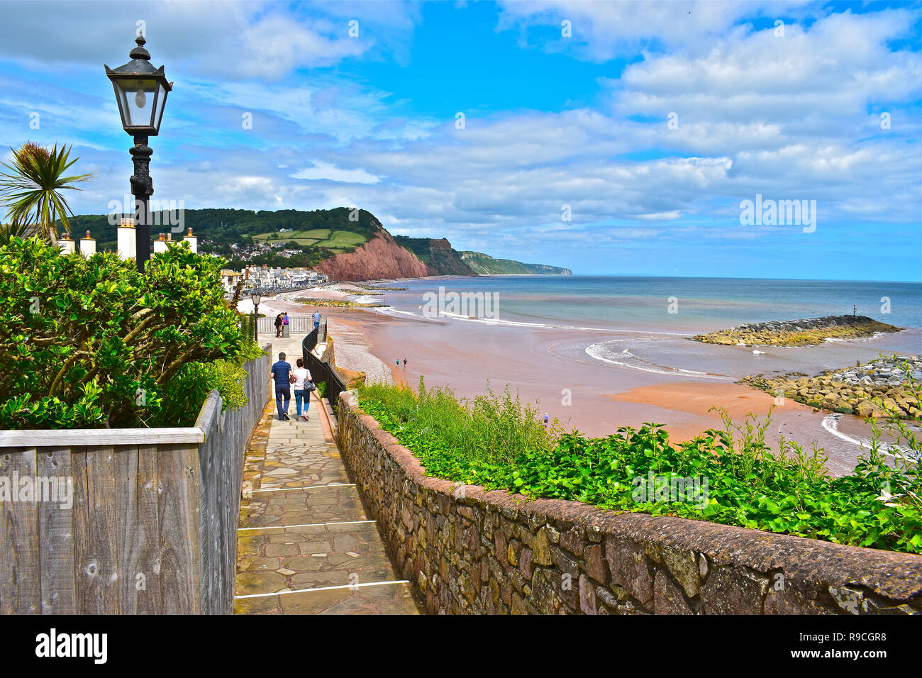 A couple walk down the coastal path leading to the picturesque seaside town of Sidmouth in Devon, with distant cliffs of the Jurassic Coast. - Stock Image