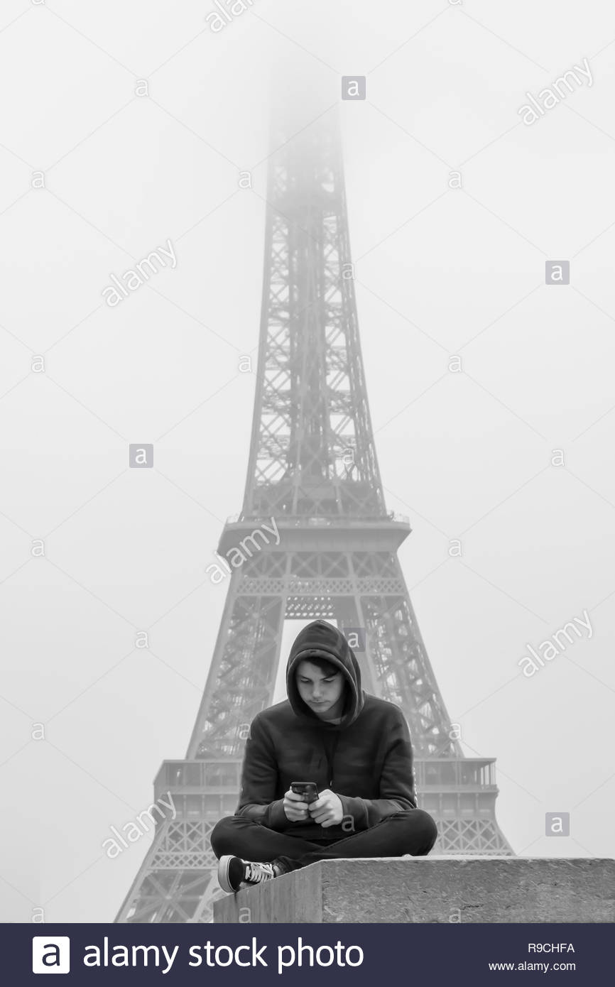 Paris, France, october 22, 2018: a young man with his smartphone in front of eiffel tower - Stock Image