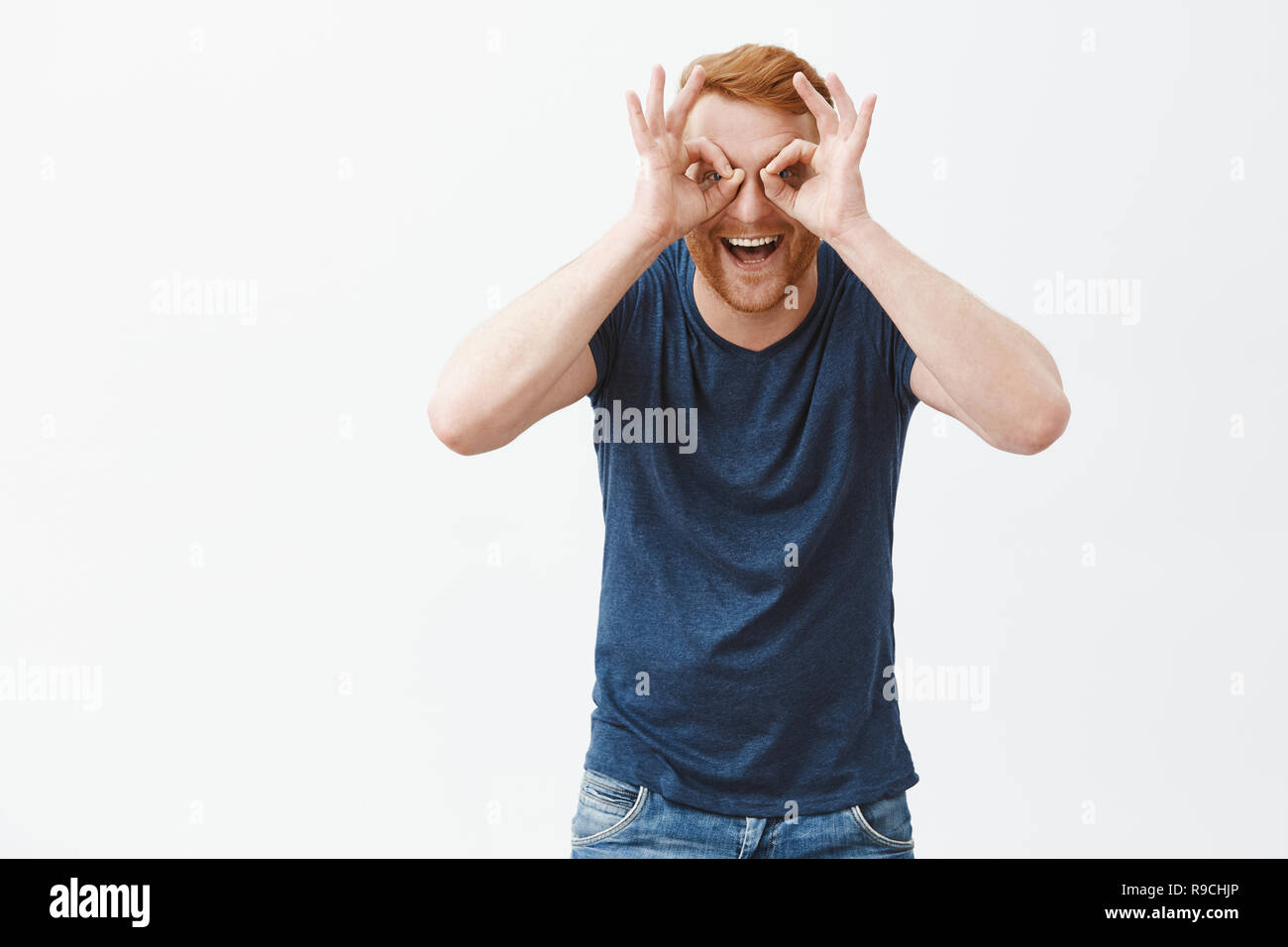 Man is large child. Joyful and playful emotive redhead guy with bristle, showing zero or okay gesture over eyes as if looking trought binocular, smiling happily and gazing at camera, having fun - Stock Image