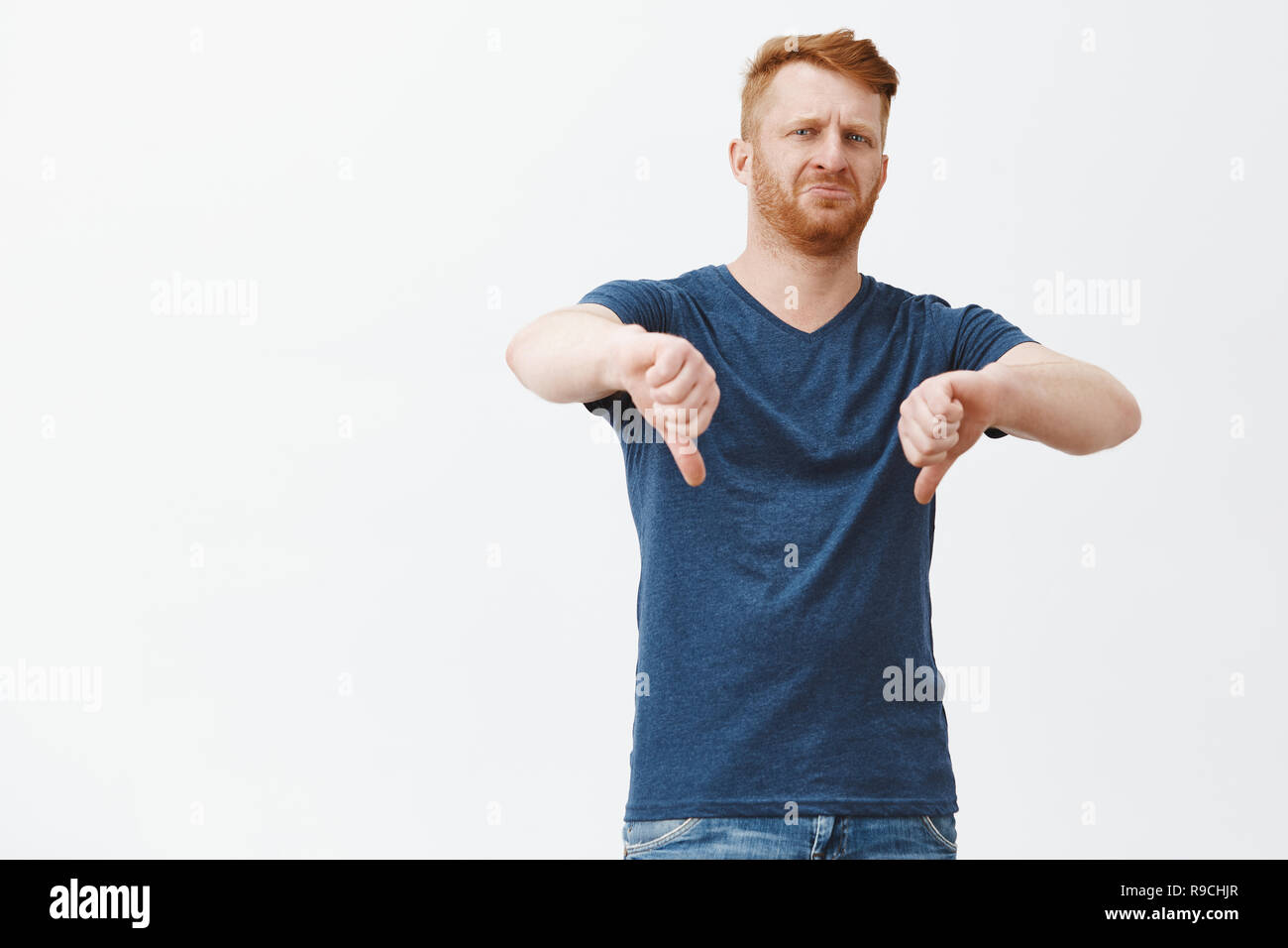 What and awful scene, dislike. Portrait of displeased, unimpressed and disgusted attractive masculine caucasian guy with red hair and brislte, frowning, showing thumbs down from disappointment - Stock Image