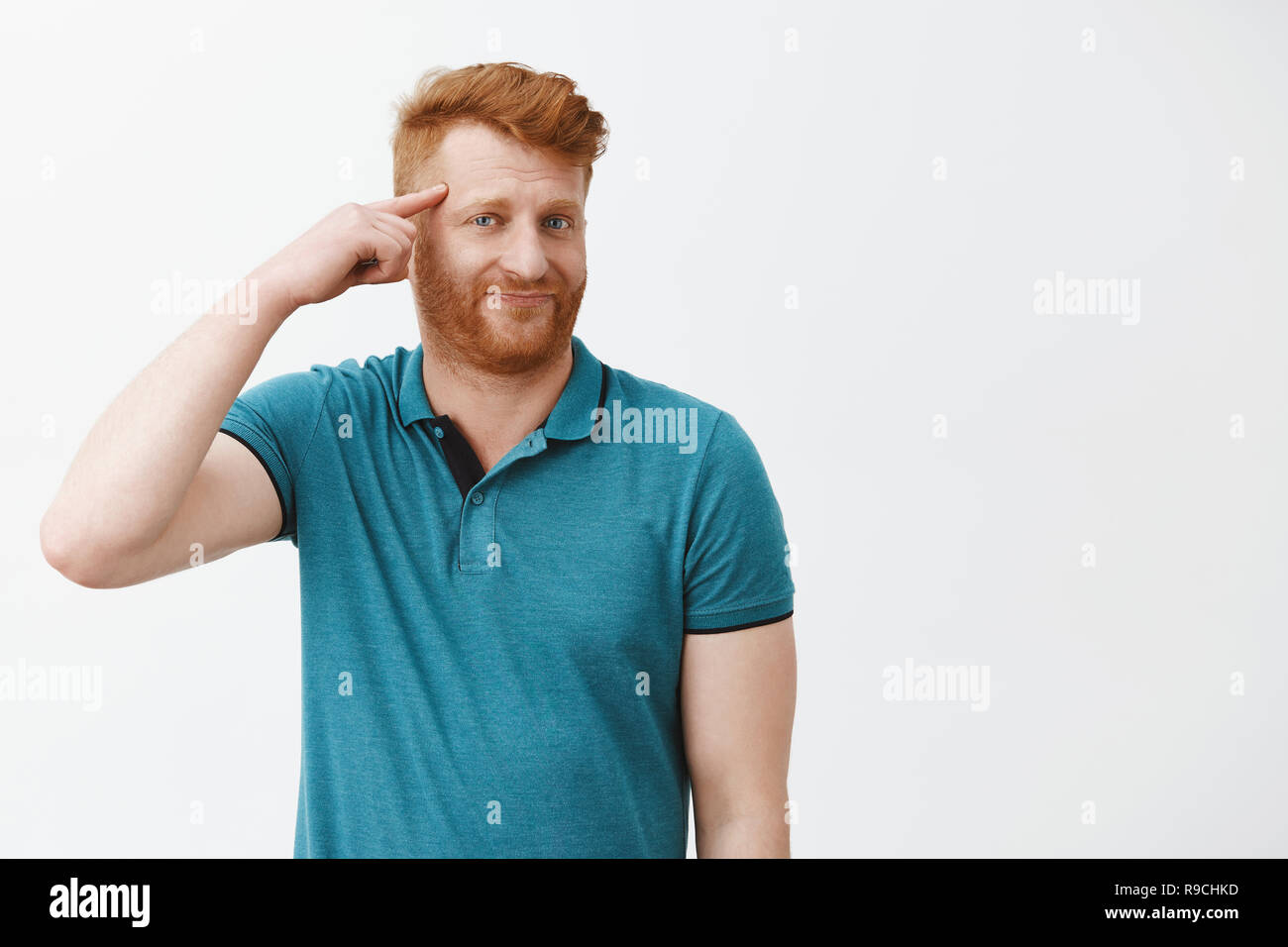 Redhead displeased guy discussing weird friend who got insane recently, making stupid decisions. Portrait of mature european man rolling finger on temple and mocking someone who make fool of himself - Stock Image