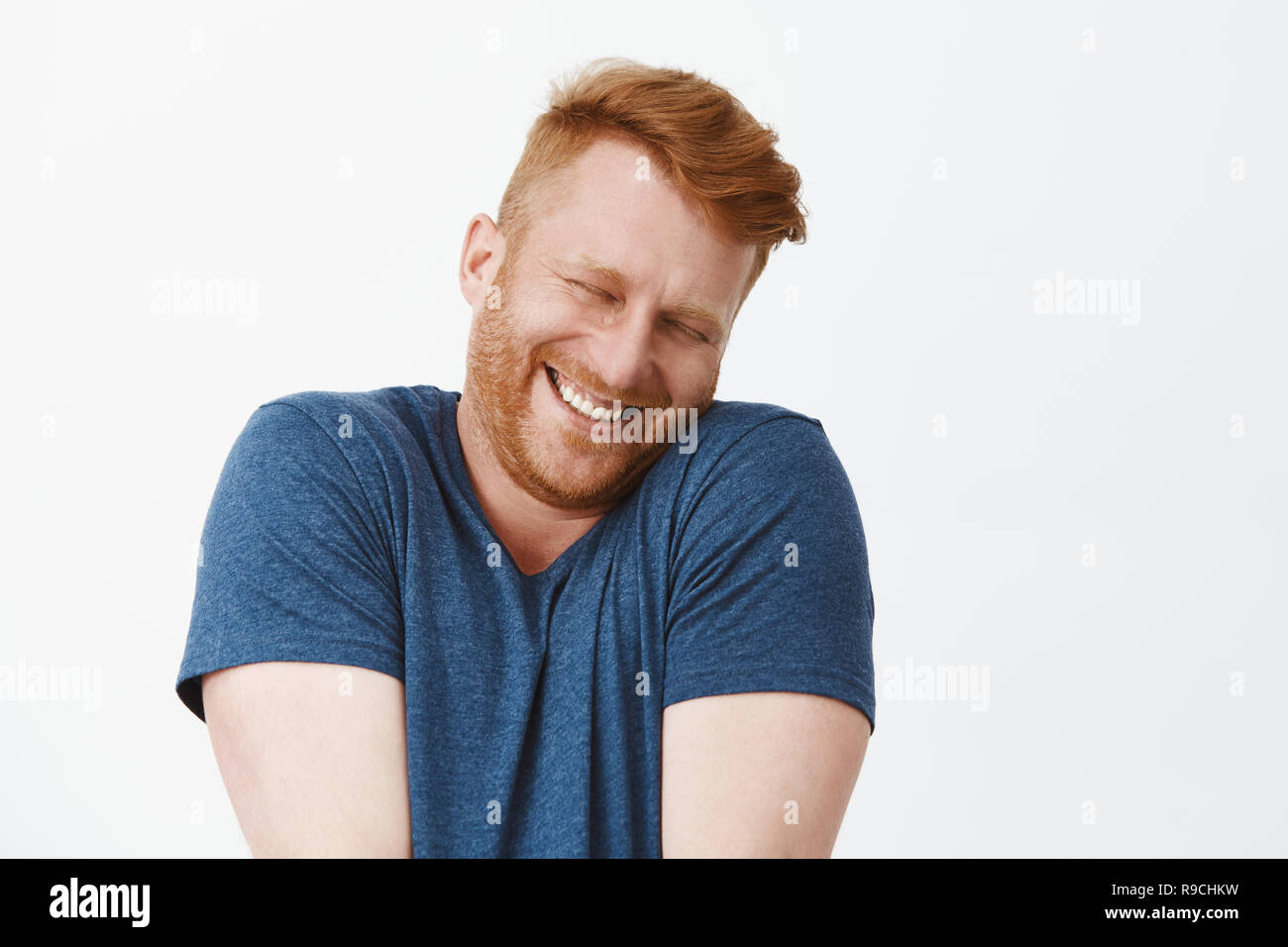 Oh stop it you. Portrait of cute pleased and satisfied happy and funny redhead man in blue t-shirt, shrugging and leaning face on shoulder while smiling broadly, blushing from joy and happiness - Stock Image
