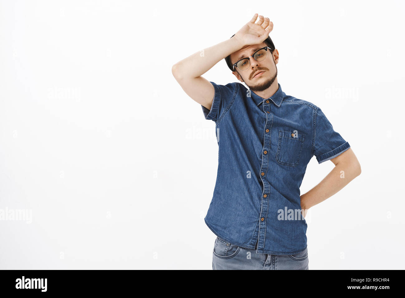 Man feeling tired and upset no one helps him whiping sweat of forehead with arm holding hand on waist gazing down with unhappy sad expression standing exhausted and concerned over gray background - Stock Image