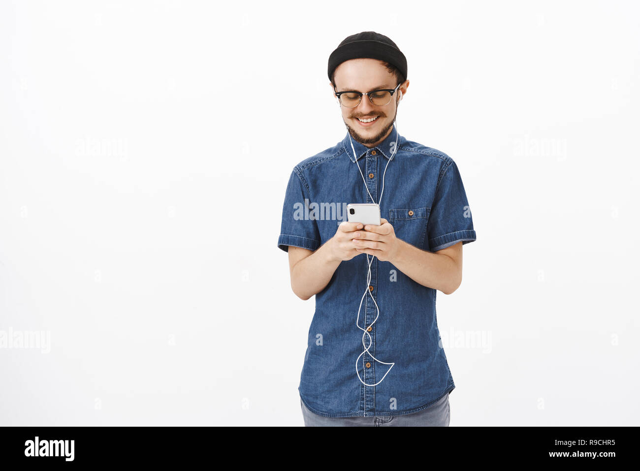 Charming and joyful handsome adult guy in beanie and glasses with beard messaging during travel in subway holding smartphone listening music in earbuds, satisfied with cute romantic note - Stock Image
