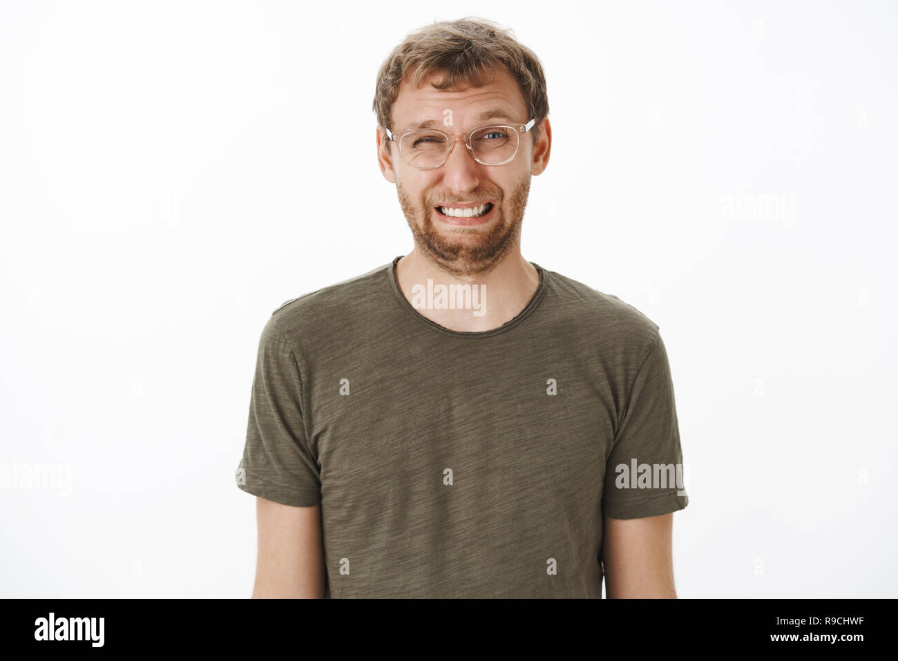Guy squinting and making funny face eating sour lemon frowning and wrinkling nose standing disgusted and dissatisfied over white background in transparent glasses and green t-shirt - Stock Image