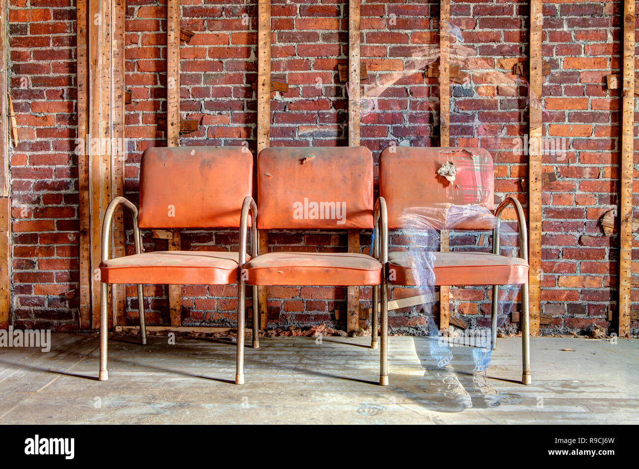 Ghostly image of a man sitting on an orange chair fading away see-through body in abandoned building. - Stock Image