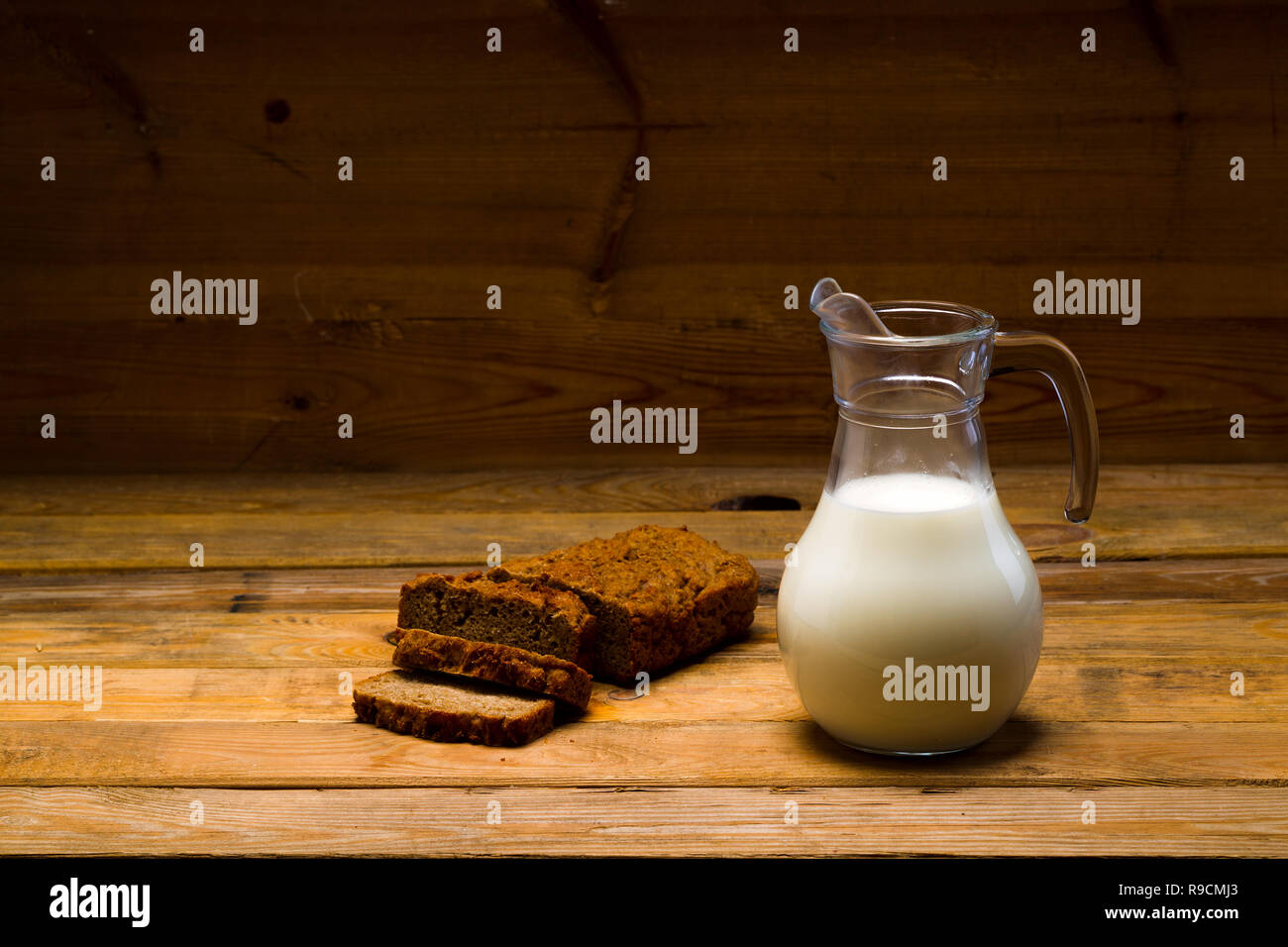 Milk from a glass jug poured into a glass, a loaf of rye bread, ears of corn on the background of wooden boards, studio light - Stock Image