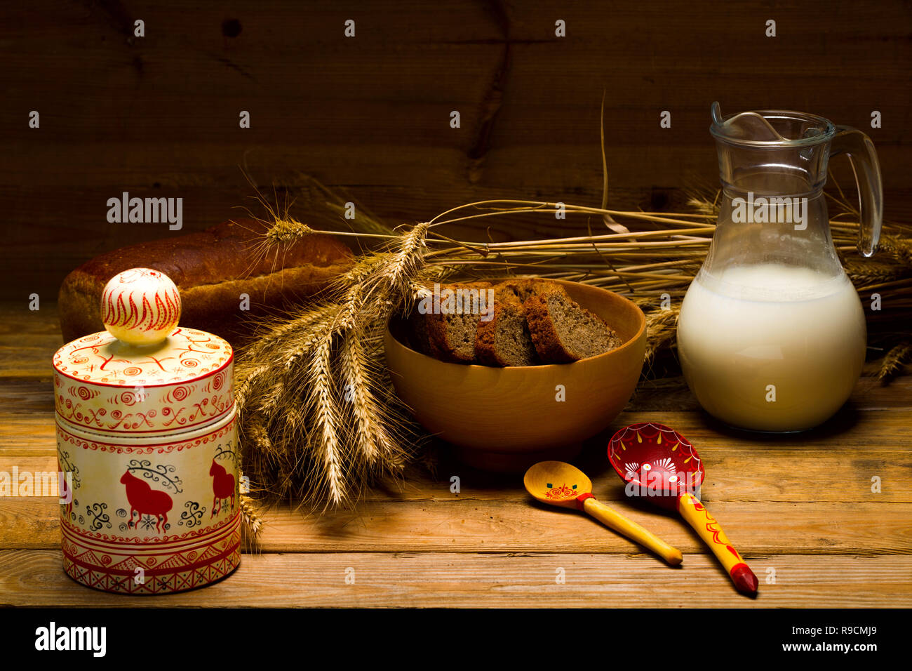 Still life with a glass jug of milk, a glass mug, rye bread, ears of corn on the background of wooden boards - Stock Image