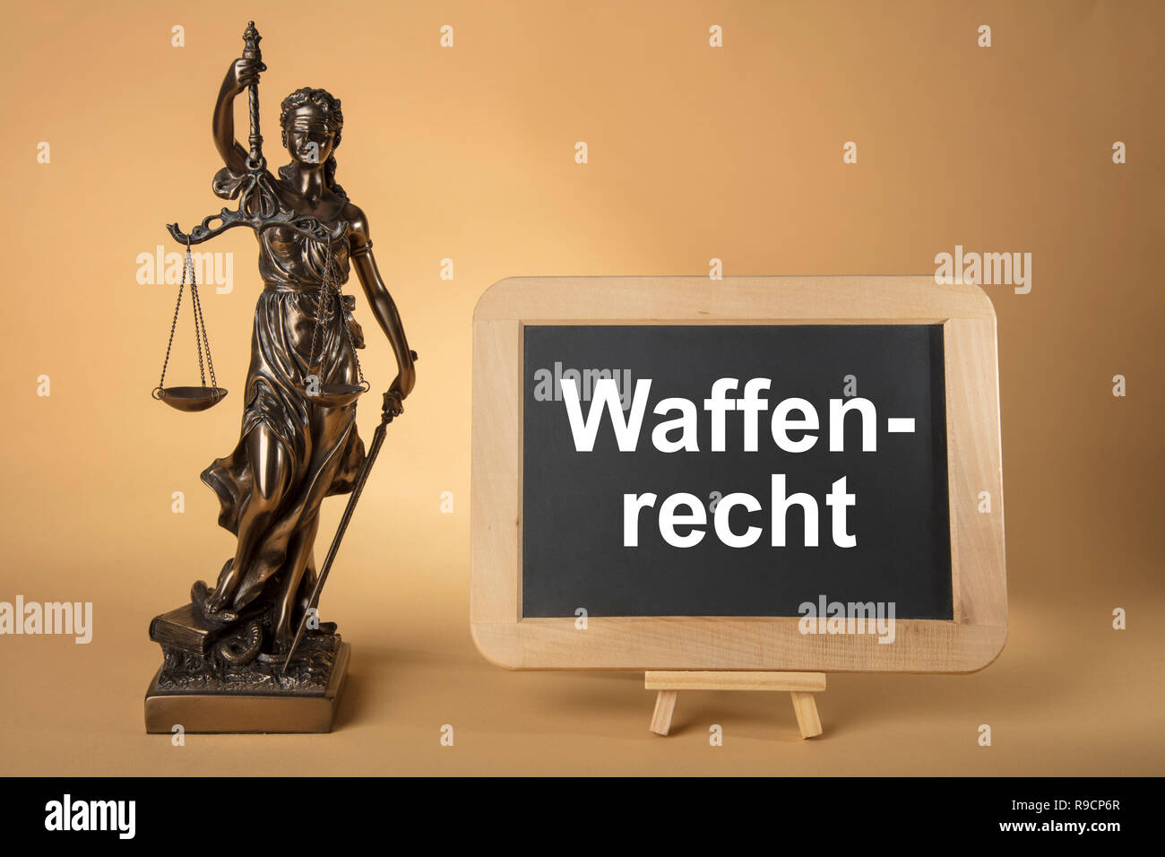 Justizia Figure with chalkboard with german text: Weapons Legally on beige Background - Stock Image