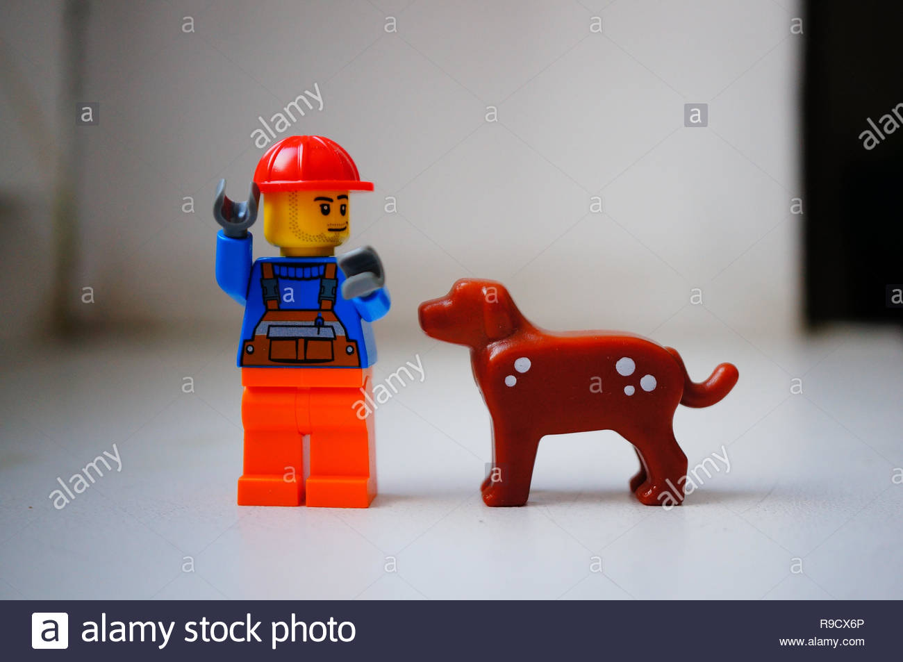 Poznan, Poland - December 22, 2018: Lego construction worker standing next to his best dog friend in soft focus background.  - Stock Image