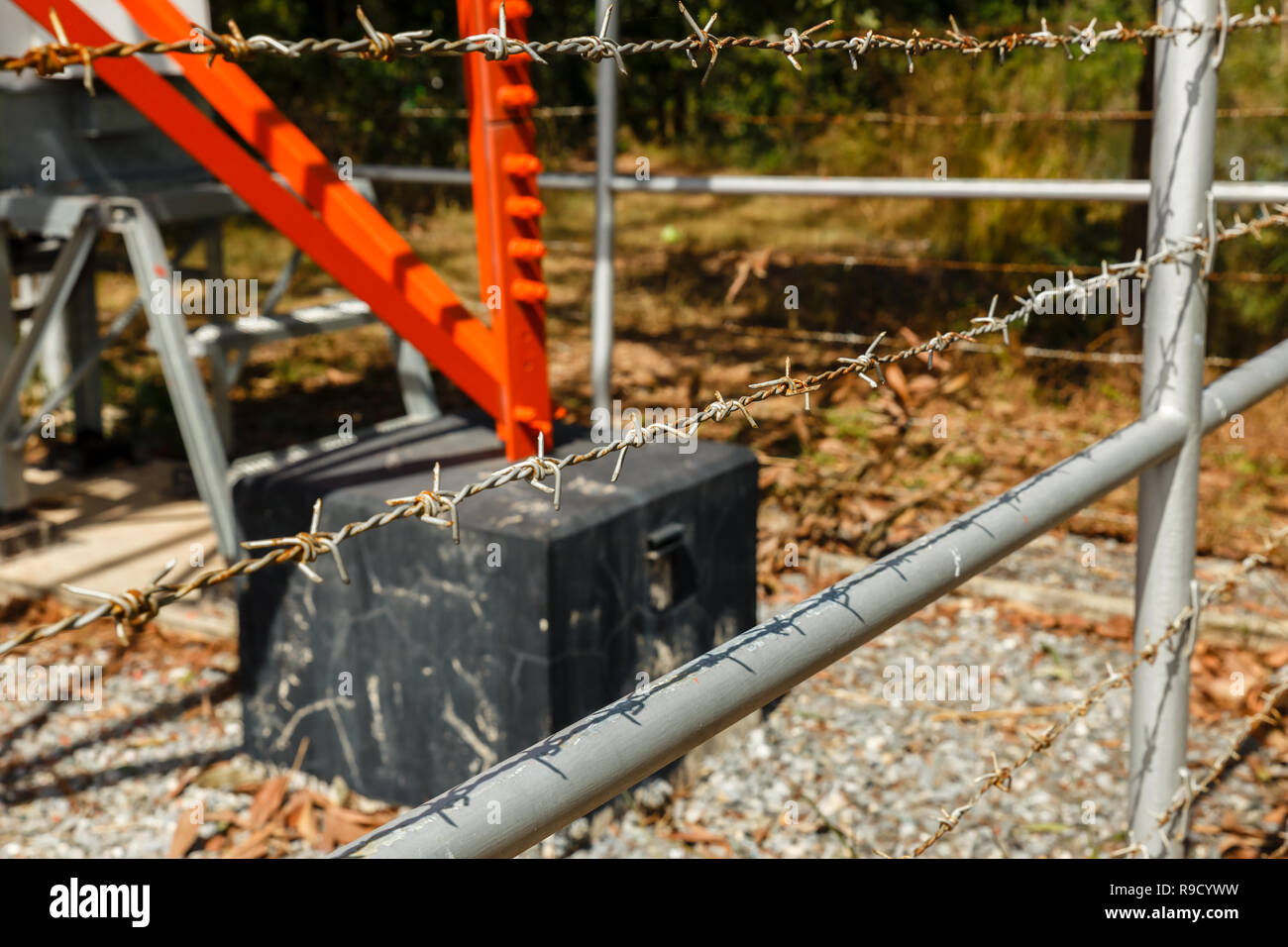 barbed wire fence around cell tower - Stock Image