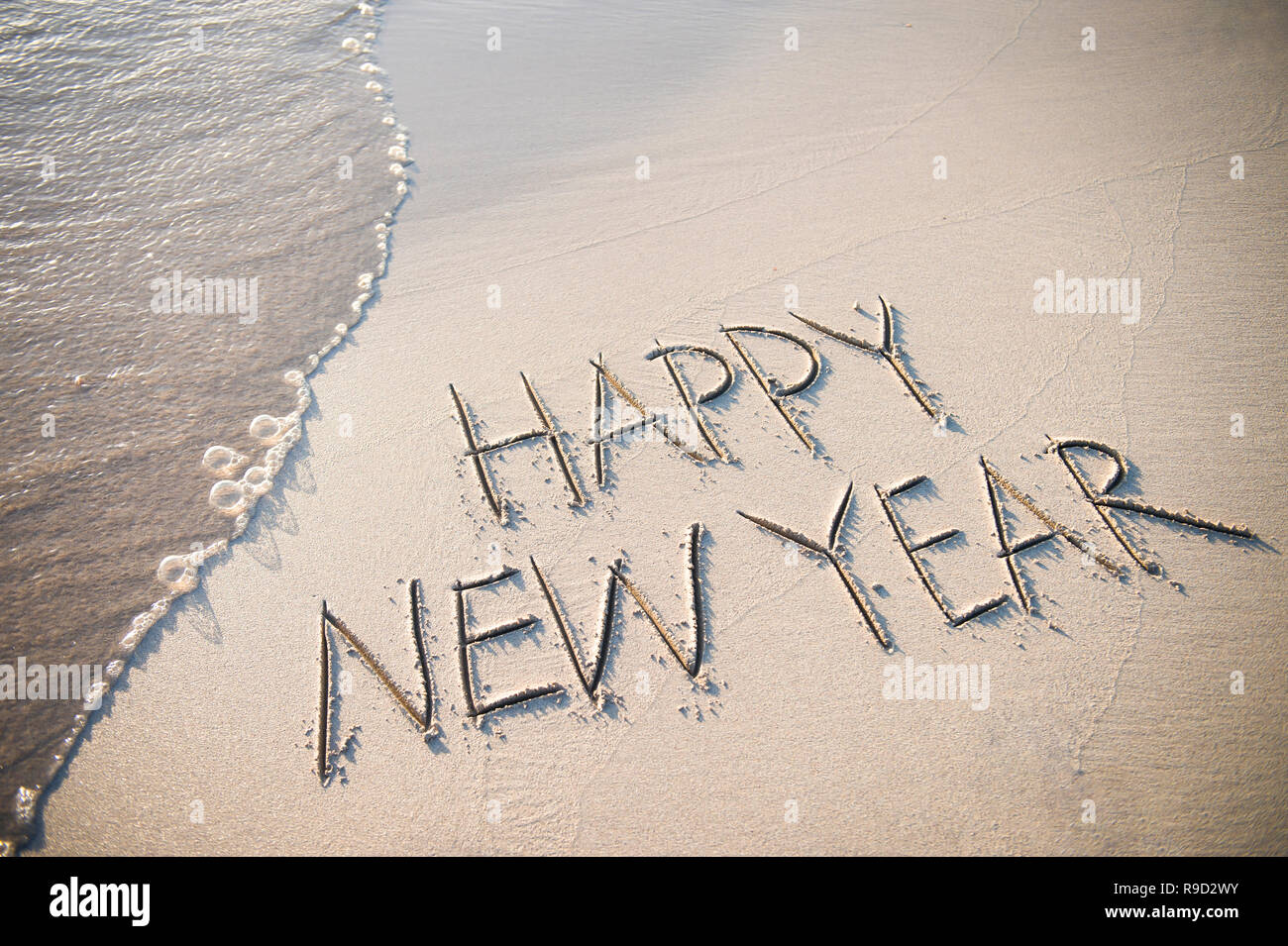 Happy New Year message handwritten in smooth, clean sand with a fresh wave coming up the beach - Stock Image
