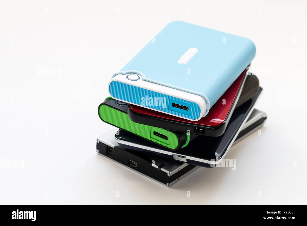 Stack of five different types of portable external hard drives with USB connection socket on end. Generic no name. Deep focus. Plain white background. - Stock Image