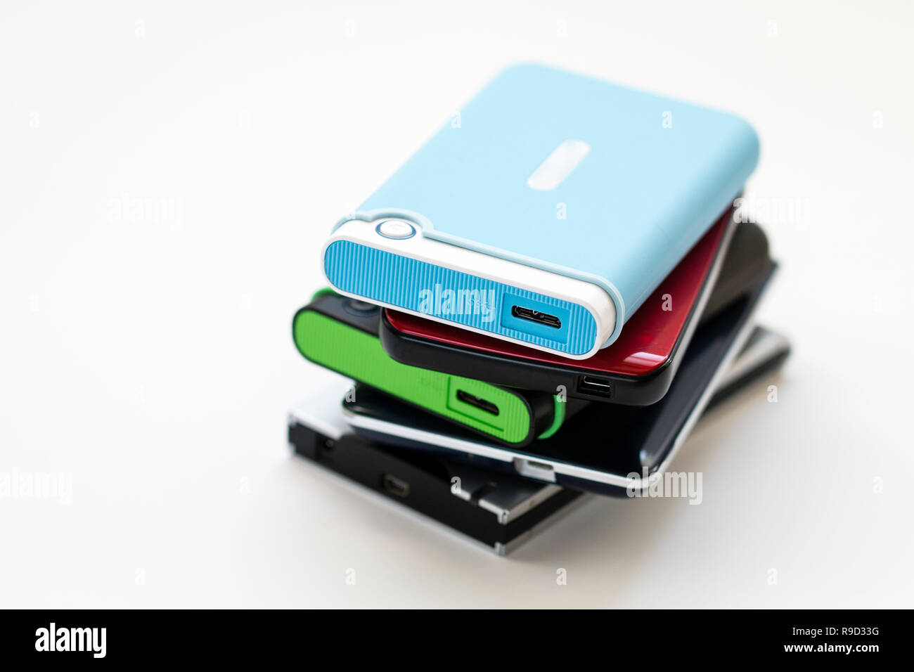 Stack of five different types of portable external hard drives with USB connection socket. Generic no name. Shallow focus. Plain white background. - Stock Image