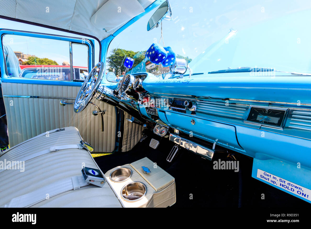 1957 Chevrolet Bel Air car. Interior by front passenger seat, fluffy dice hanging from mirror, light blue dashboard, sign, 'Heaven is a 57'. - Stock Image