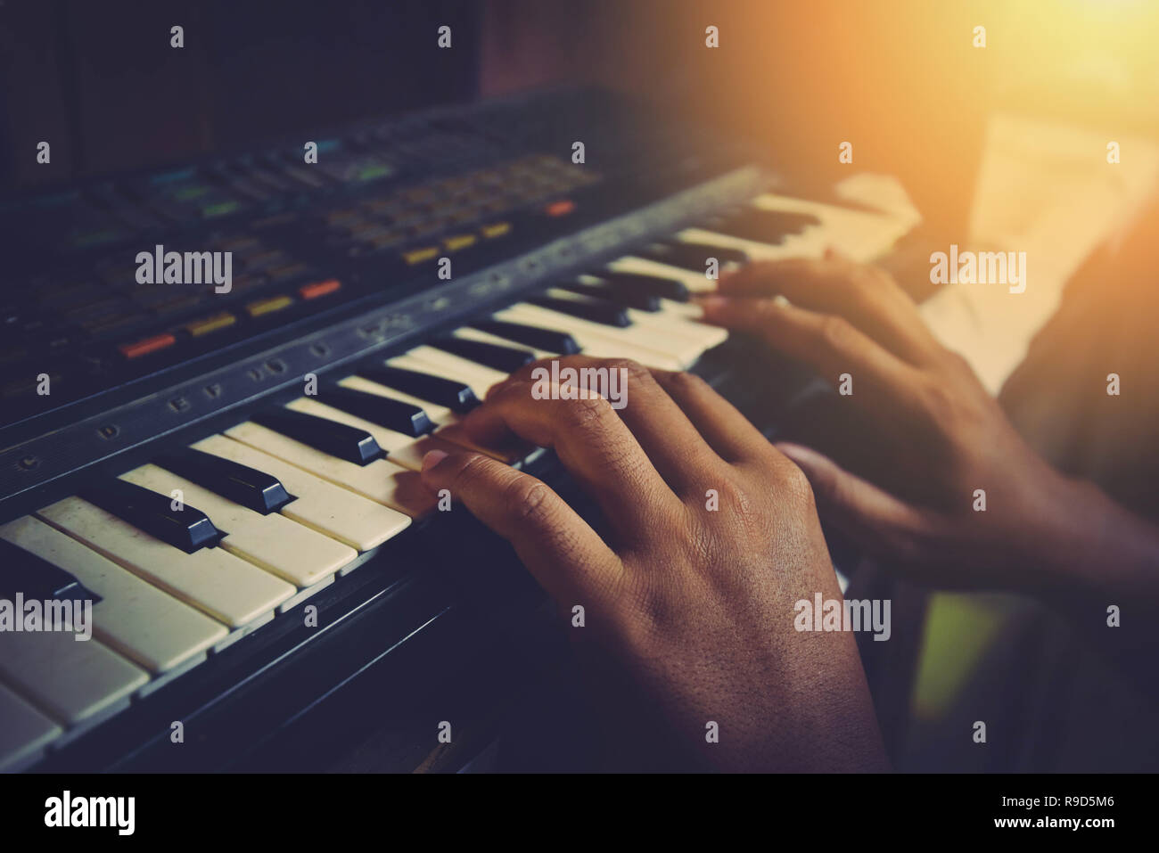 synthesizer piano player musician playing keyboar / MIDI keyboard electronic hands playing different chords on old piano keys on dark background vinta - Stock Image