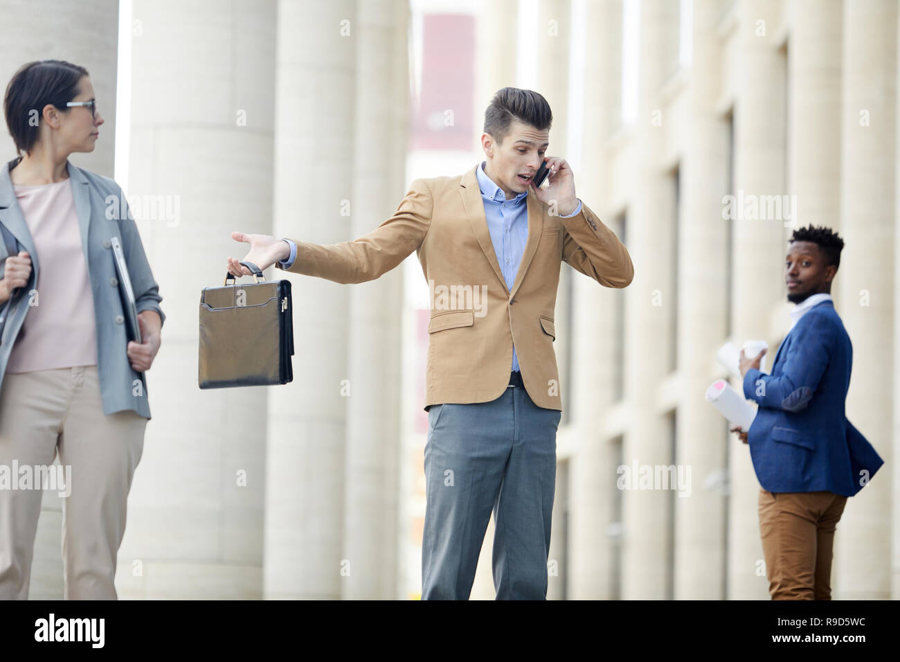 Puzzled businessman talking on phone loudly - Stock Image