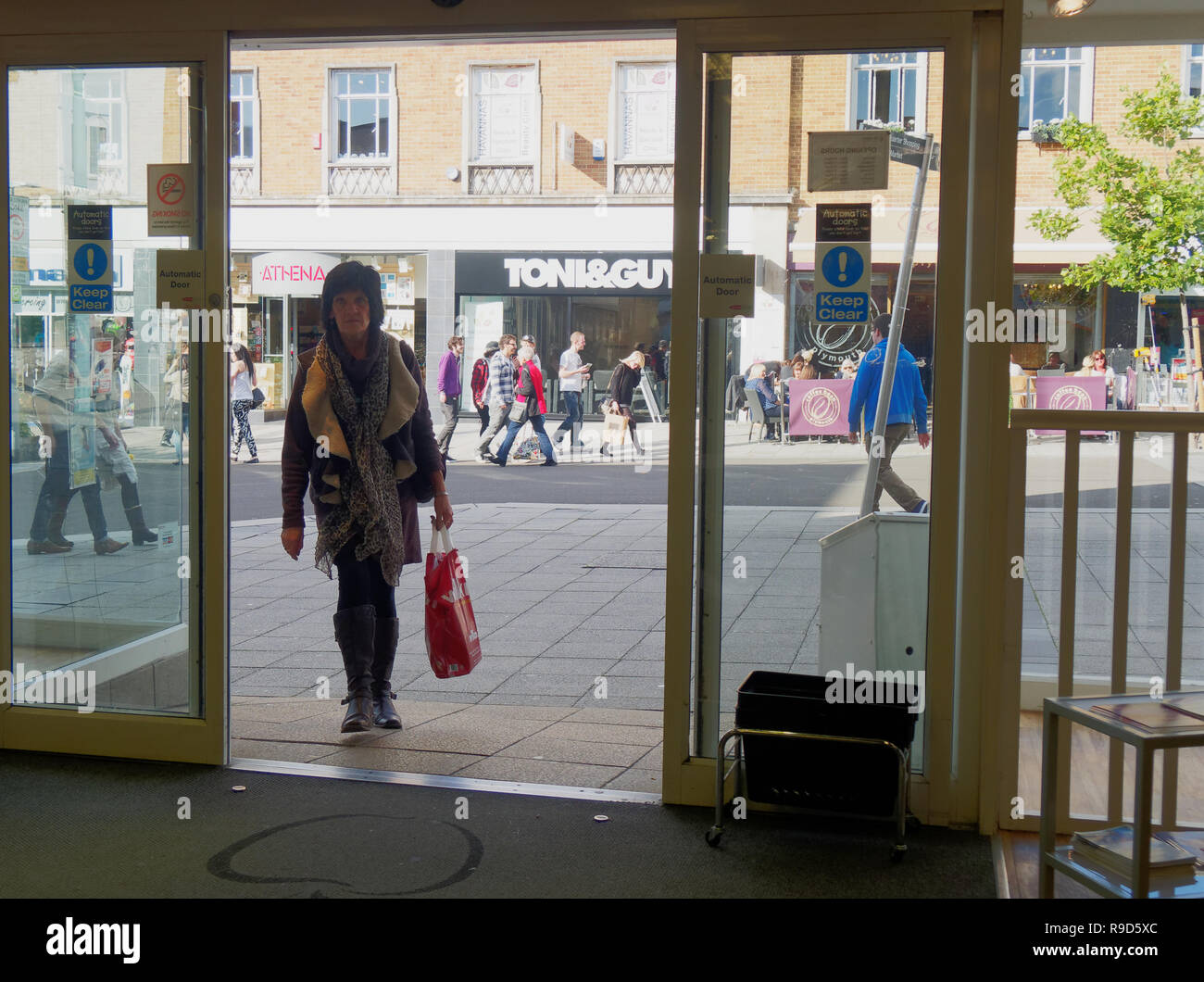 UK High street shoppers shopping and visitors browsing shop fronts - Stock Image