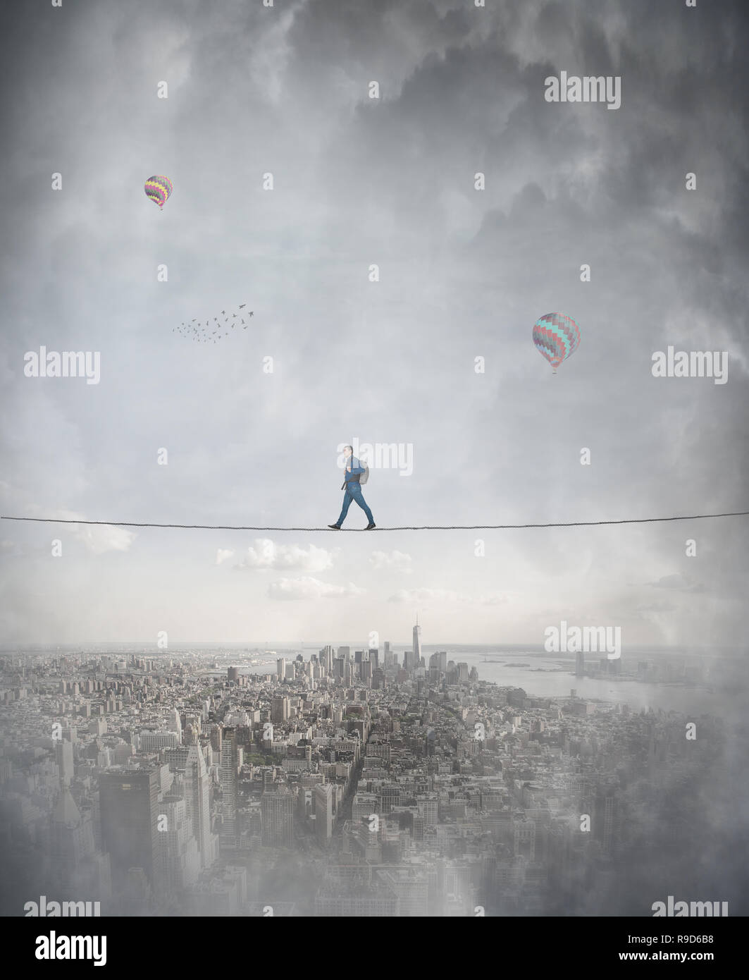 Young woman silhouette balancing on slackline rope high above clouds between two imaginary parallel worlds. Walking confident on tightrope. Conquering - Stock Image